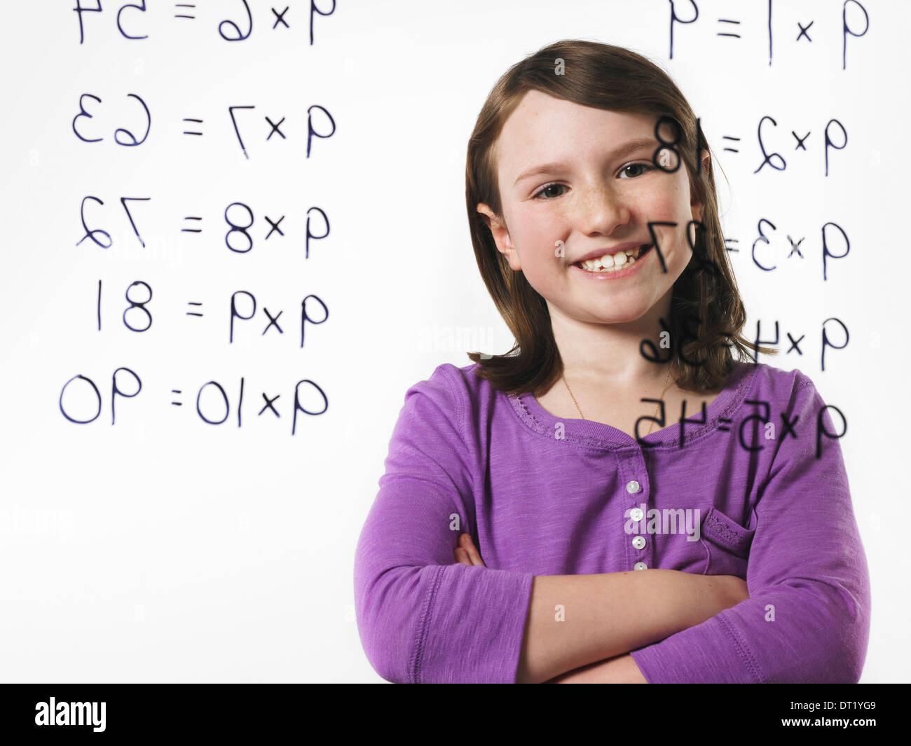 Un enfant à la recherche lors d'une série de tables de multiplication écrite sur une surface à voir Photo Stock