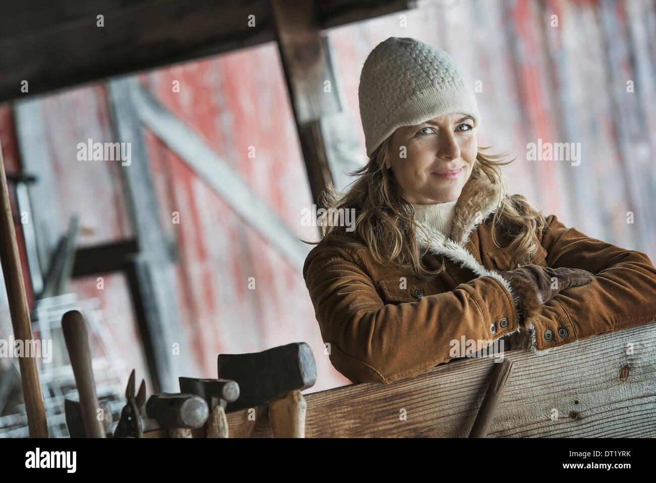 Une femme dans un manteau de mouton une rangée d'outils à main accroché à un poste Photo Stock