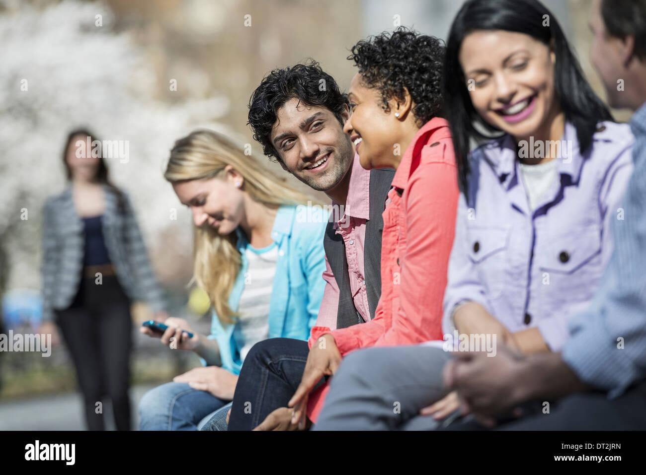 Cinq personnes sont assises en ligne dans le parc Photo Stock