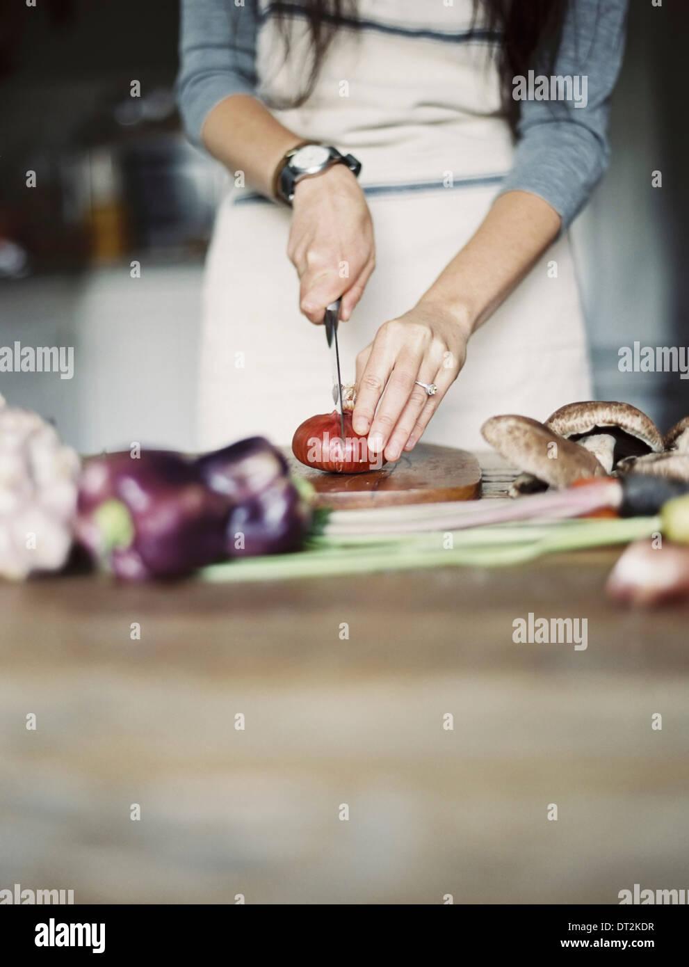 Une cuisine domestique une table top Jeune femme couper des légumes frais avec un couteau Photo Stock