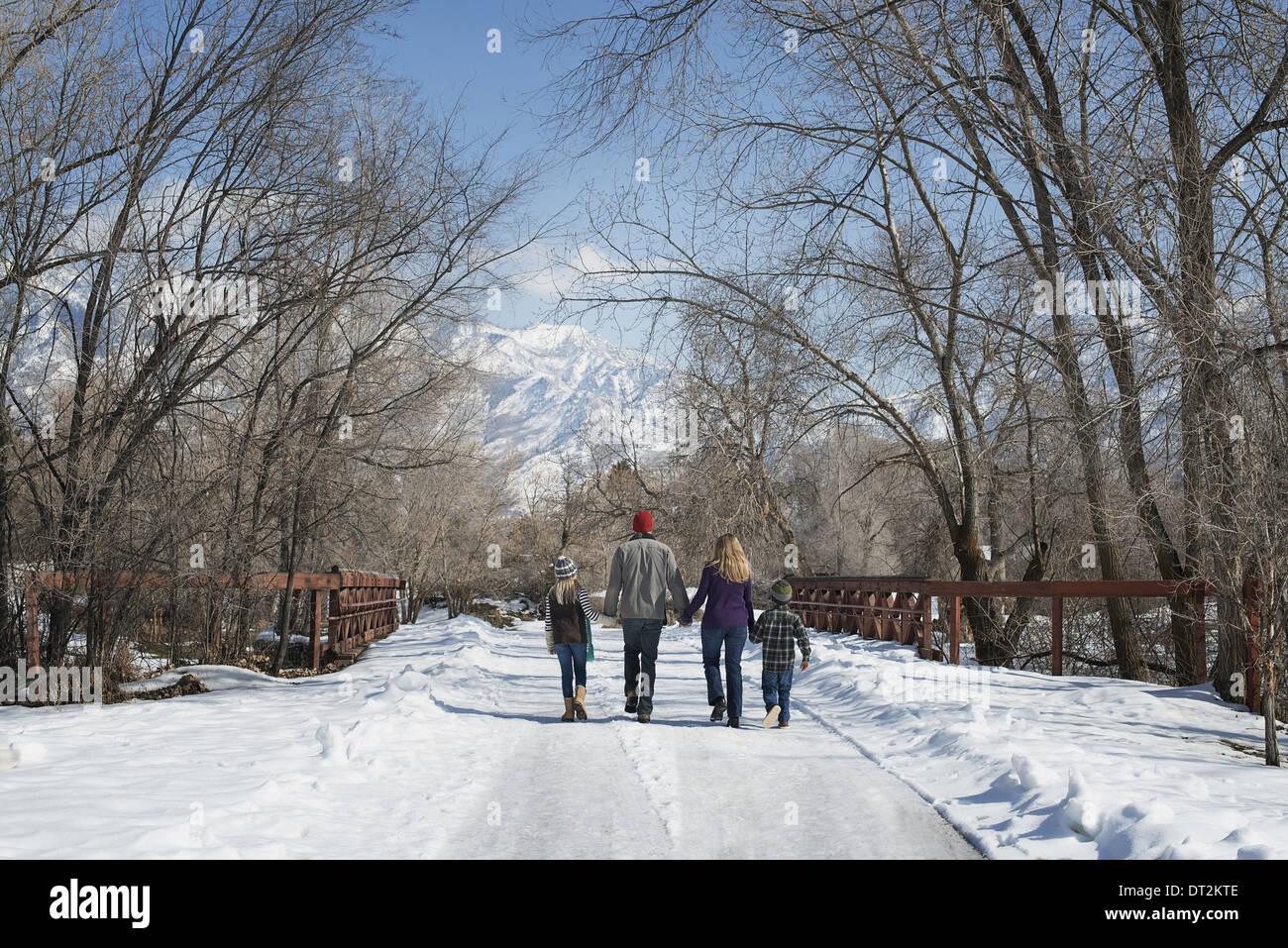 Paysage d'hiver avec neige au sol une famille adultes et deux enfants marchant sur une route vide Photo Stock