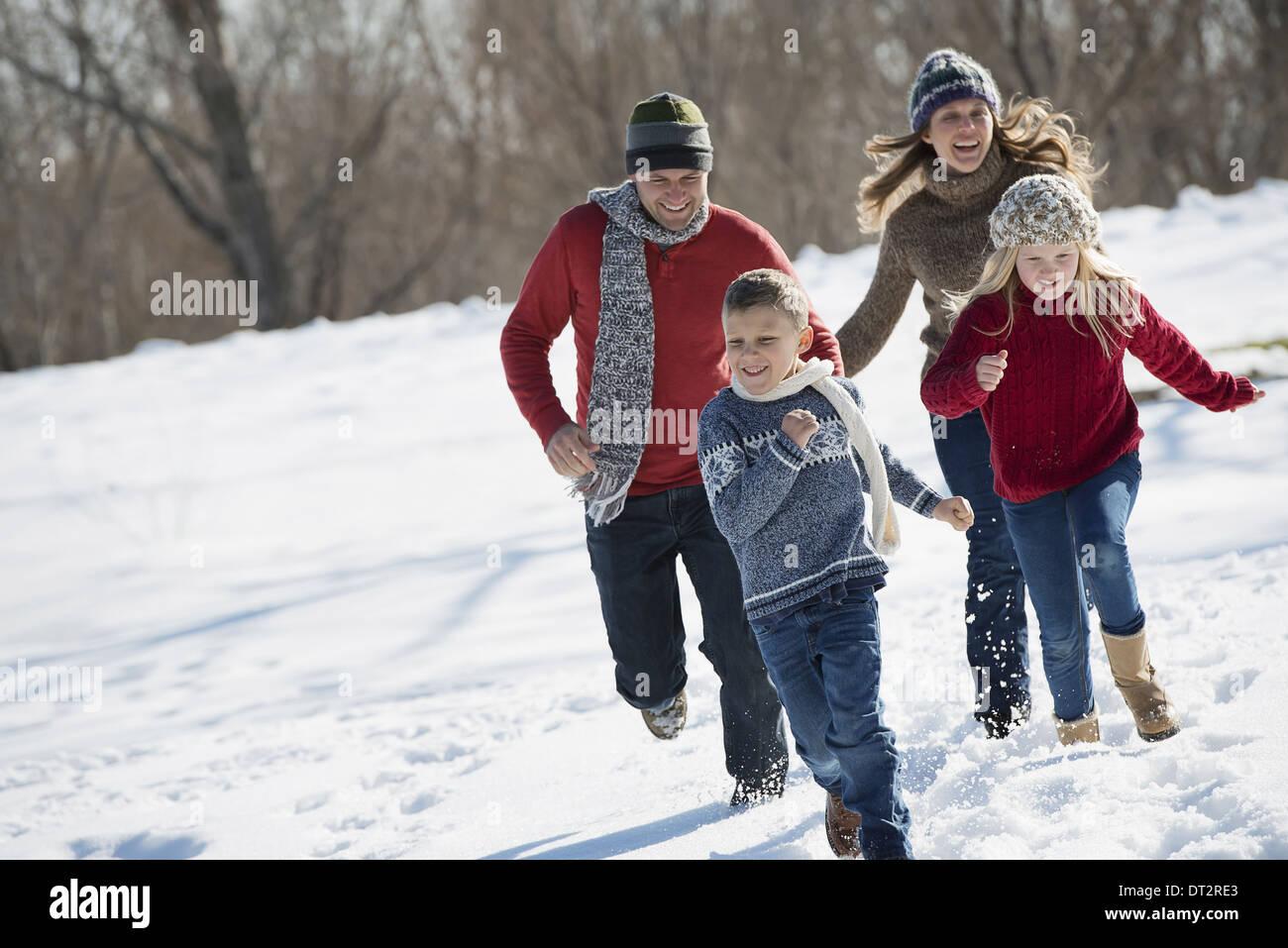 Paysage d'hiver avec neige au sol famille marcher deux adultes courir après deux enfants Banque D'Images