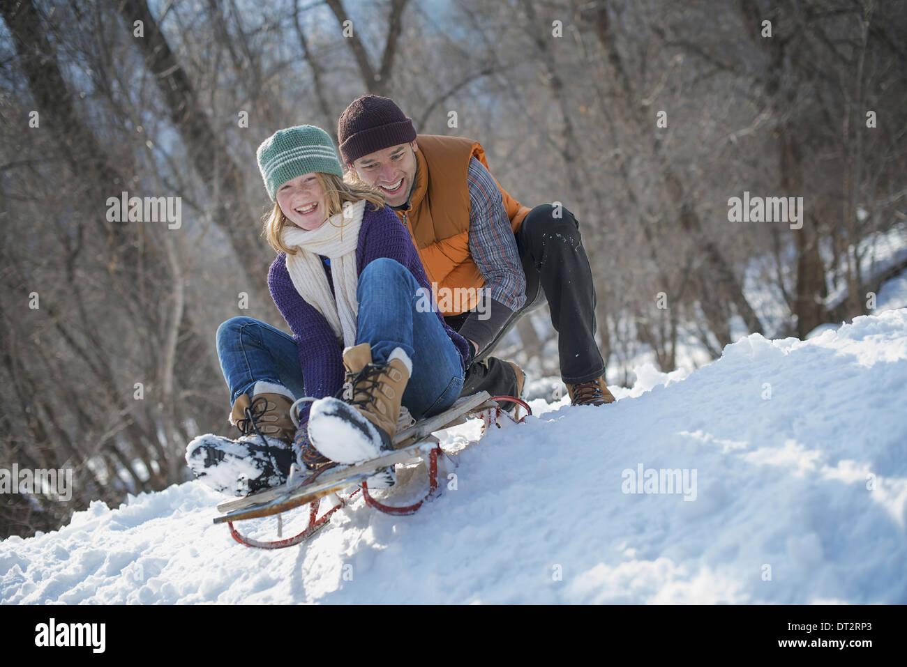 Paysage d'hiver avec neige au sol un homme poussant une jeune femme du haut d'une pente sur un toboggan Banque D'Images