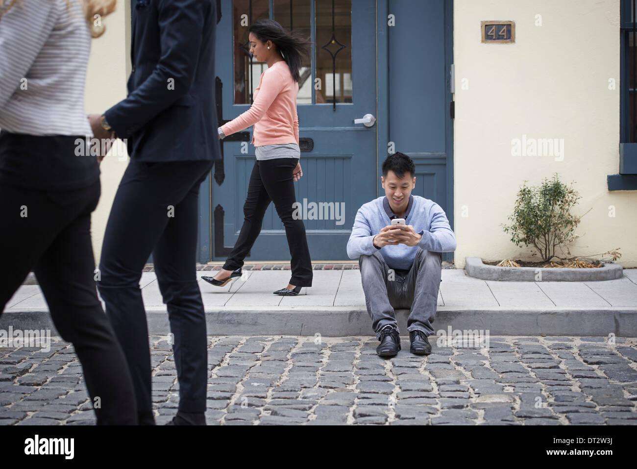 Les jeunes à l'extérieur sur les rues de la ville au printemps, un homme assis sur le terrain vérifier son téléphone et trois passants Photo Stock