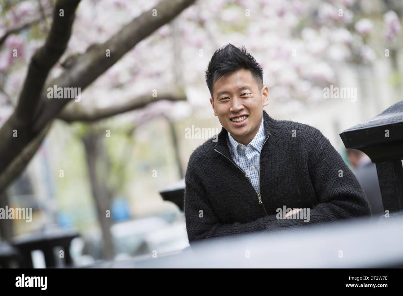 Vue sur cityA jeune homme à l'extérieur dans un parc de la ville assise sur un banc Photo Stock