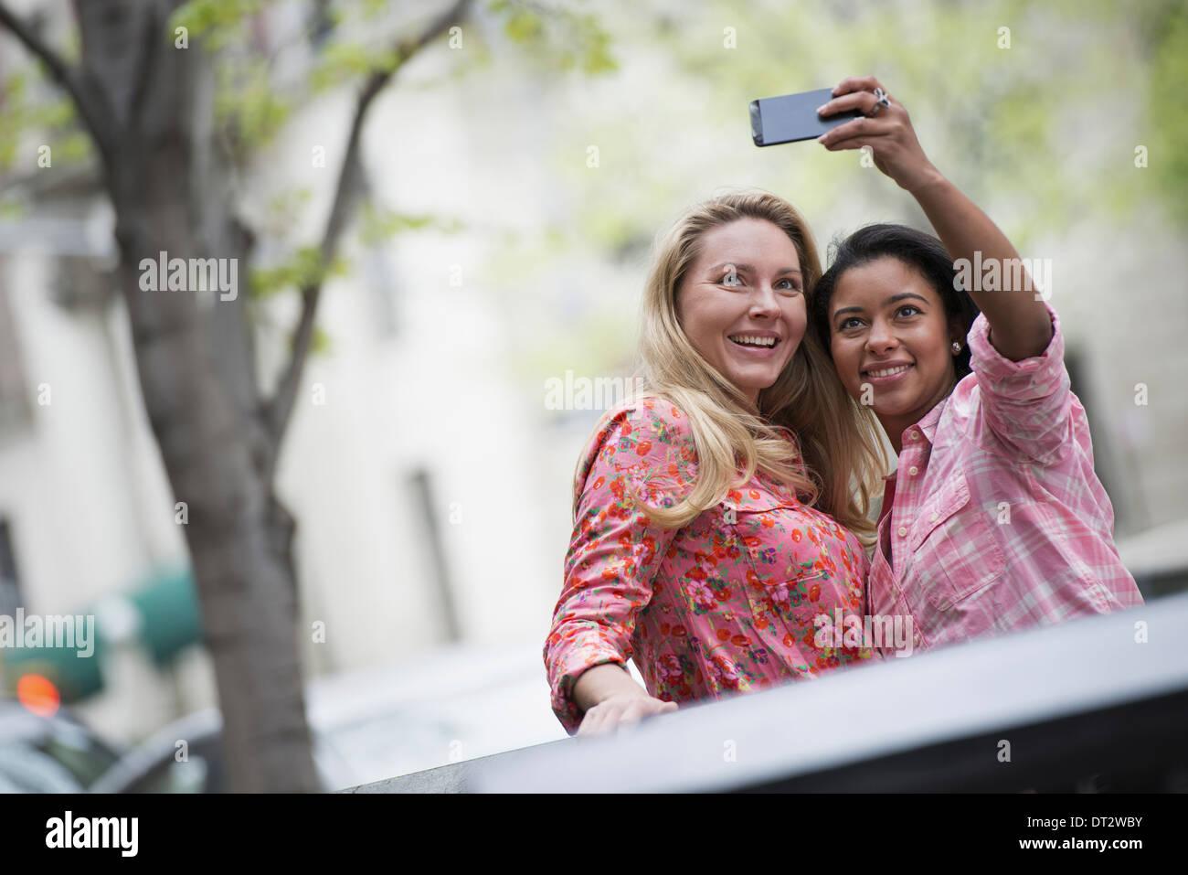 Vue sur cityYoung les gens à l'extérieur dans un parc de la ville deux femmes prenant un autoportrait ou selfy avec Banque D'Images