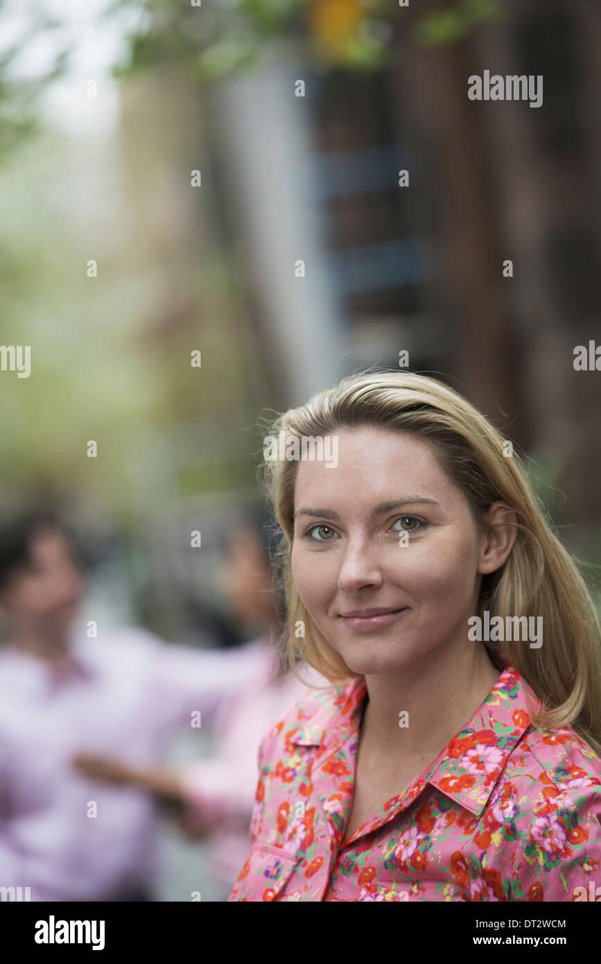 Vue sur cityA femme avec de longs cheveux blonds regardant la caméra Photo Stock