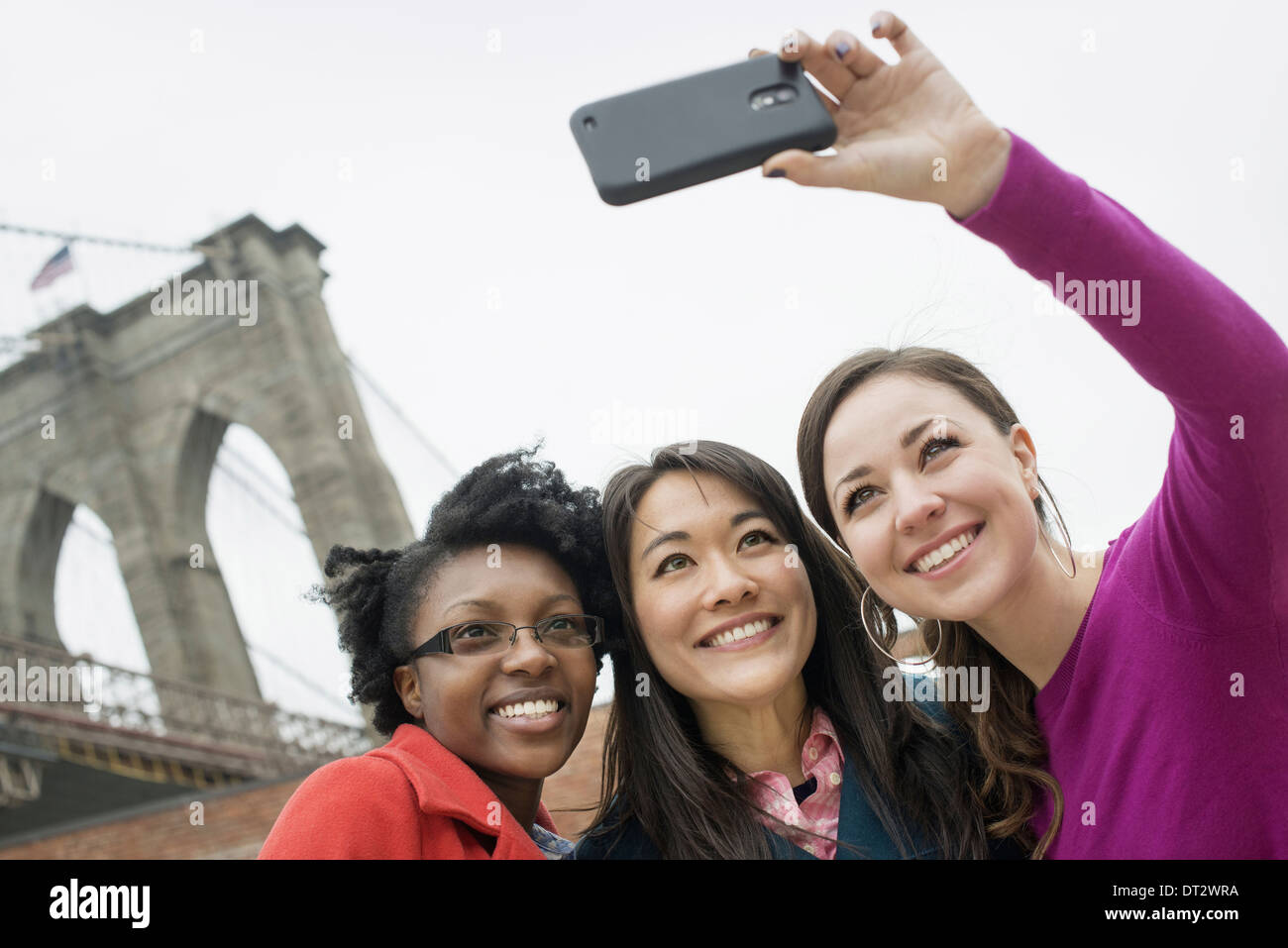 New York le pont de Brooklyn à l'Est River trois femmes dans une rangée smiling comme on prend une photo avec un téléphone intelligent Photo Stock