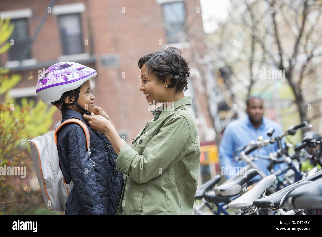 Un garçon dans un casque de vélo étant fixé par sa mère à côté d'un support à bicyclettes Photo Stock