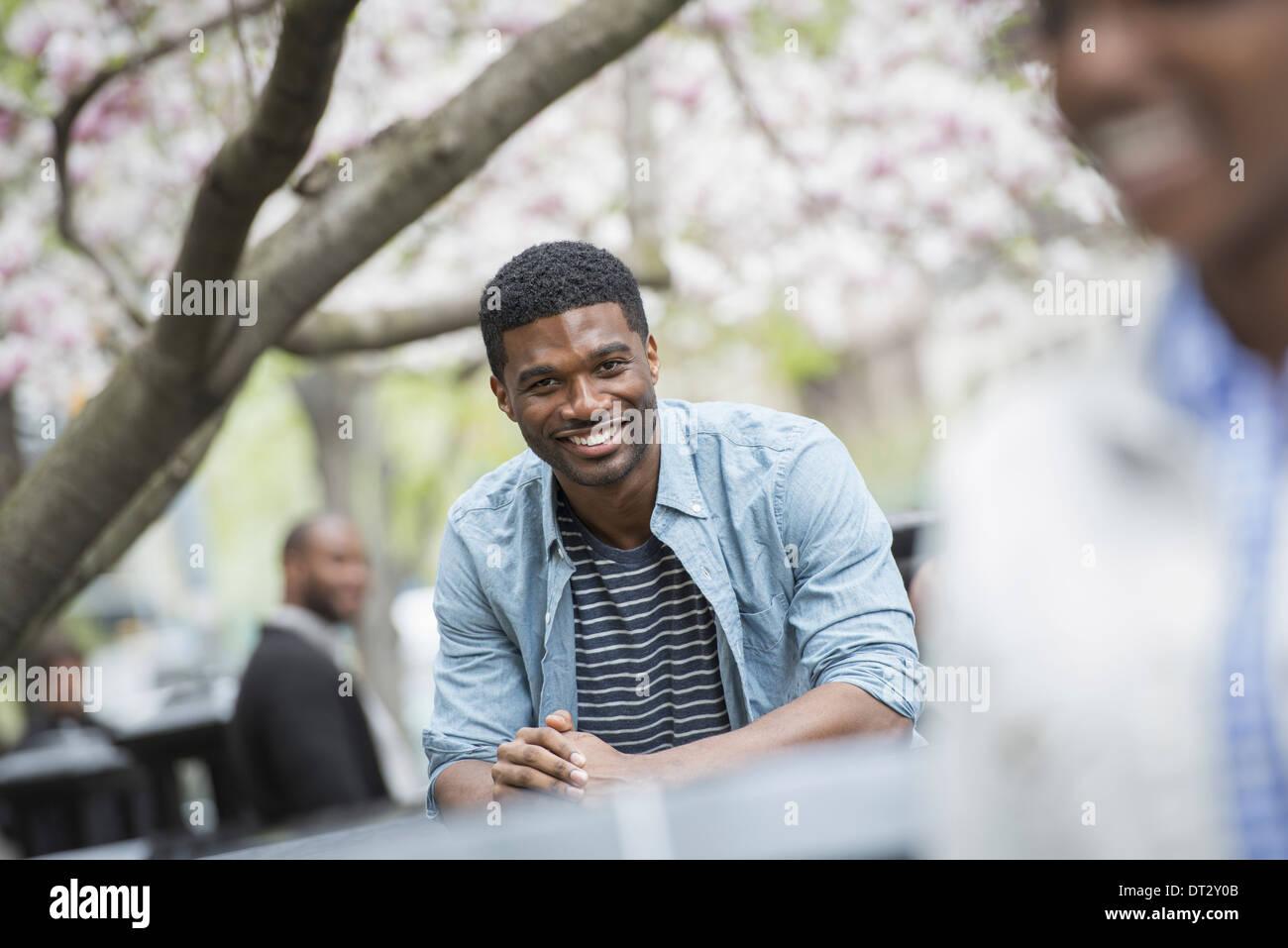Un homme assis à une table smiling une femme au premier plan Photo Stock