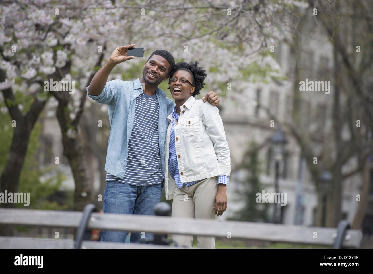 Un couple côte à côte de prendre une photo avec un téléphone intelligent Photo Stock