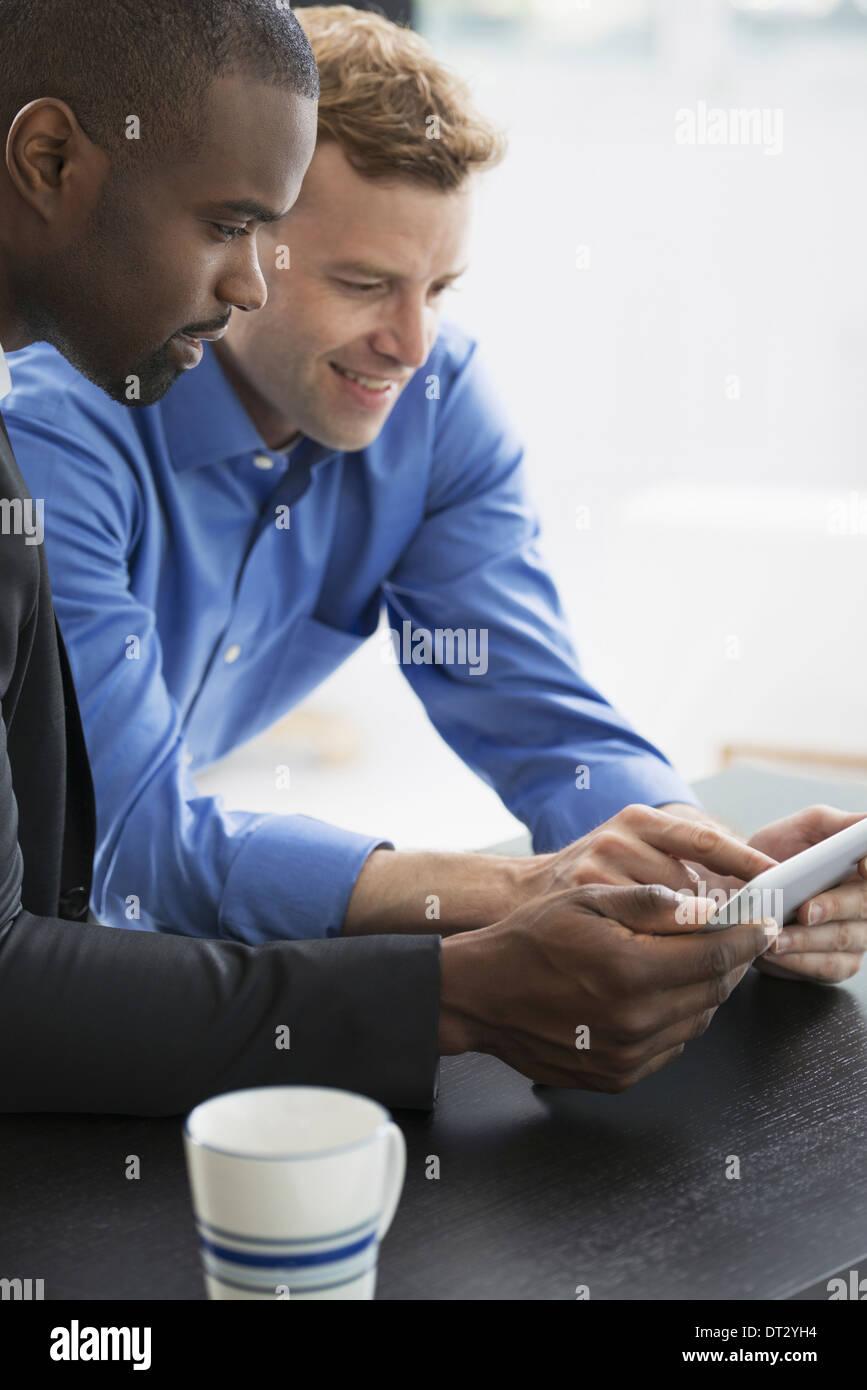 Les jeunes professionnels au travail deux hommes à la recherche d'une tablette numérique à Photo Stock