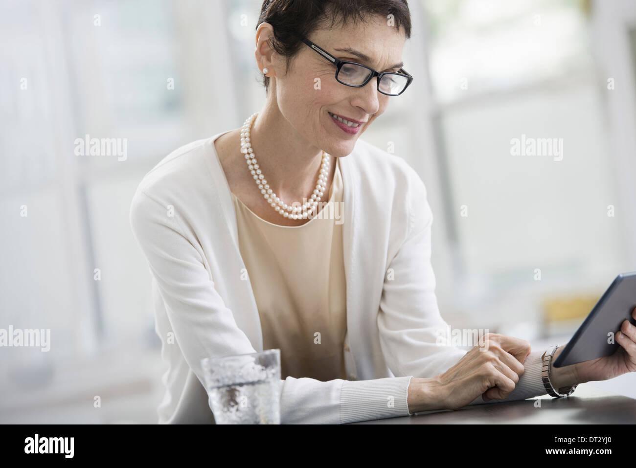 Les jeunes professionnels au travail une femme dans un bureau à l'aide d'une tablette numérique Banque D'Images