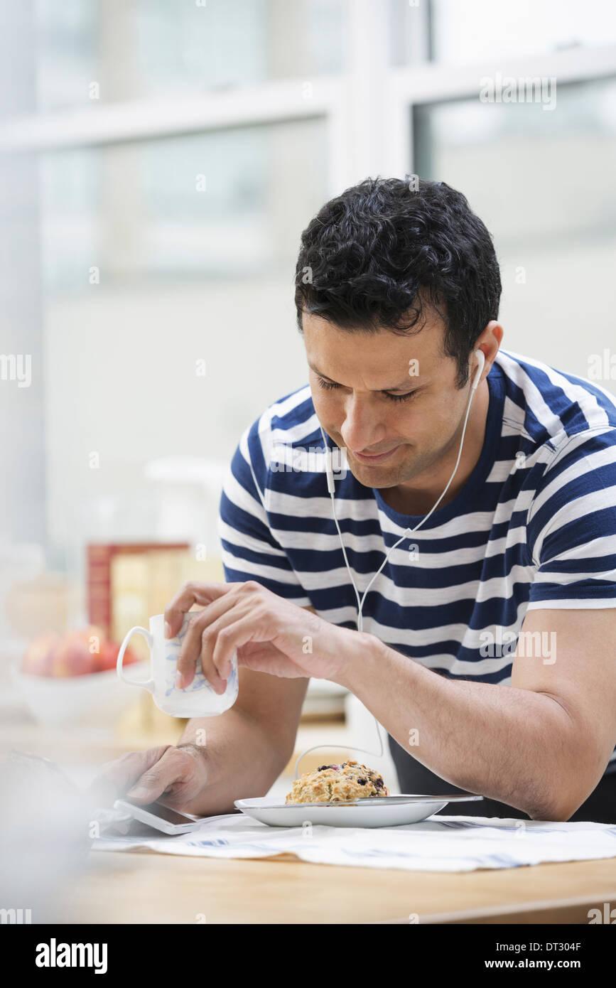 Un bureau ou un appartement à New York de l'intérieur un homme dans un tee shirt à rayures s'appuyant sur le bar de petit-déjeuner Photo Stock