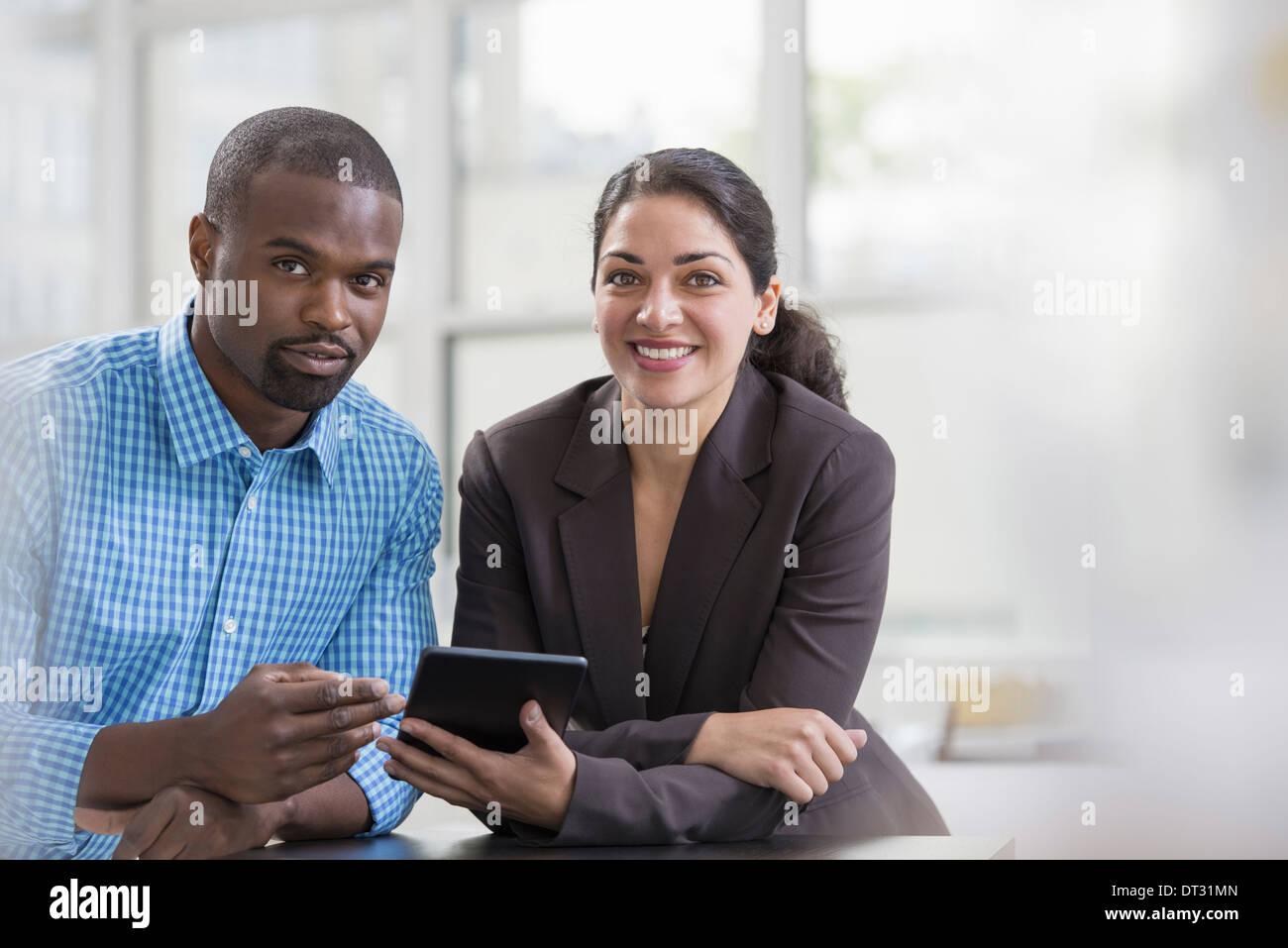 Professionnels à l'office un cadre lumineux et spacieux lieu de travail Deux personnes assis à un bureau à l'aide d'une tablette numérique, les collègues de travail Photo Stock