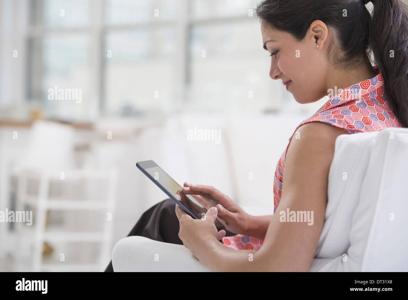 Professionnels à l'office un cadre lumineux et spacieux lieu de travail une femme assise à l'aide d'une tablette numérique Banque D'Images
