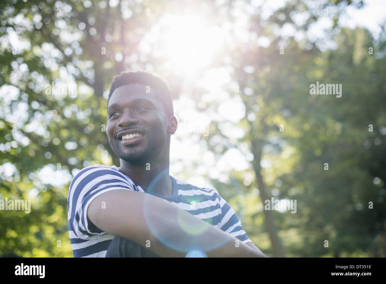 Un homme dans une chemise rayée à l'ombre des arbres Photo Stock