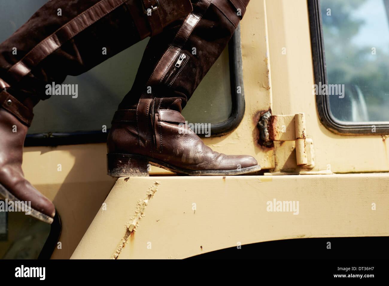 Une jeune femme en veste en jean et des bottes sur le capot d'un tracteur Photo Stock