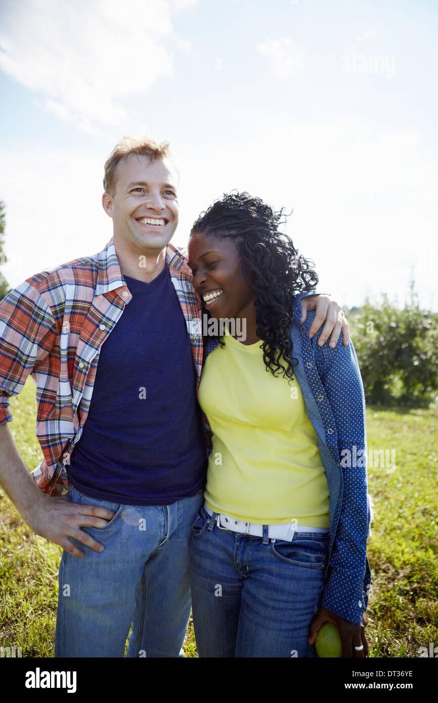 Un couple d'un jeune homme et une femme côte à côte en riant Photo Stock