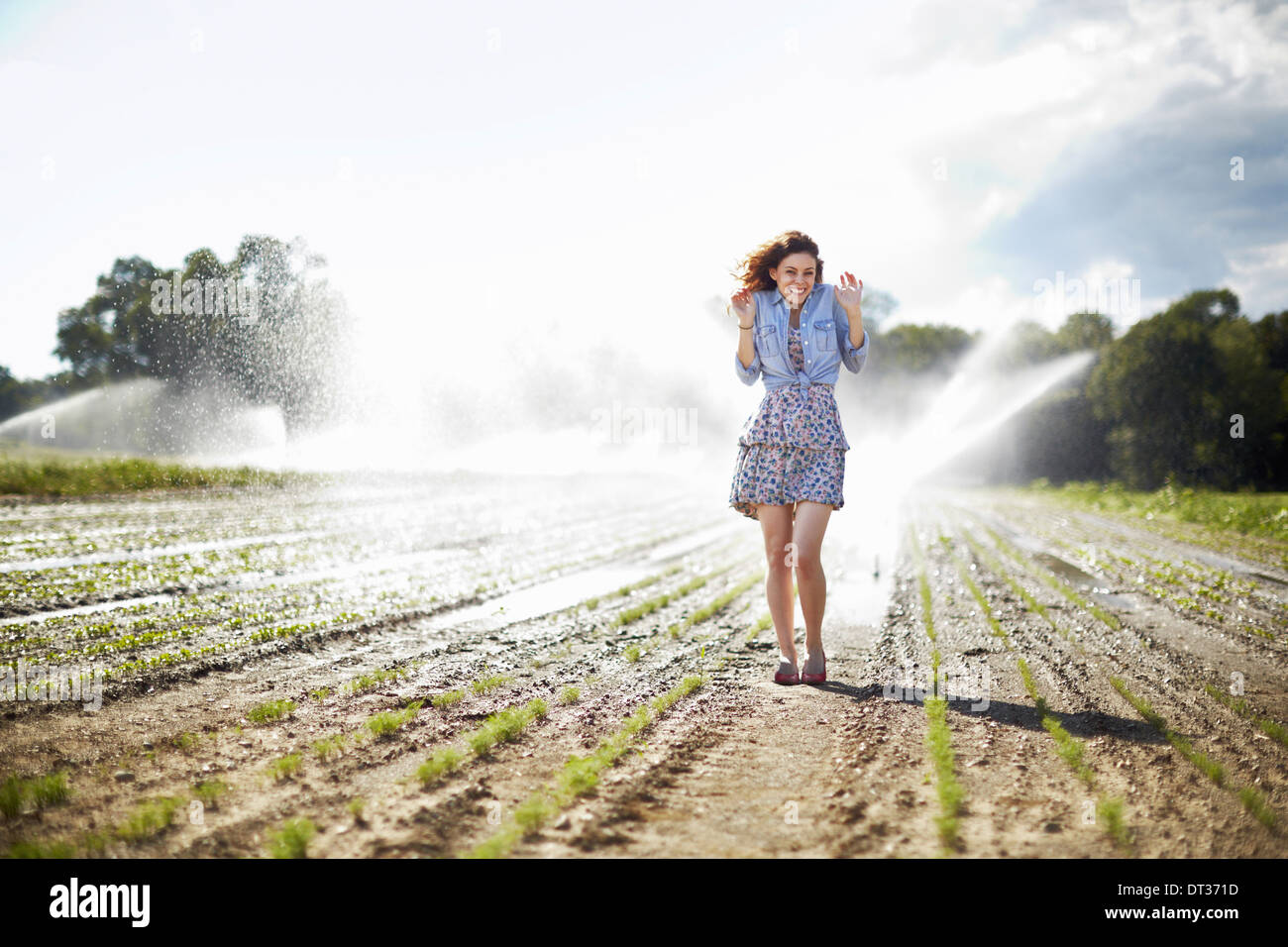 Une jeune femme en veste en jean debout dans un champ de travail sprinkleurs irrigation dans l'arrière-plan Photo Stock