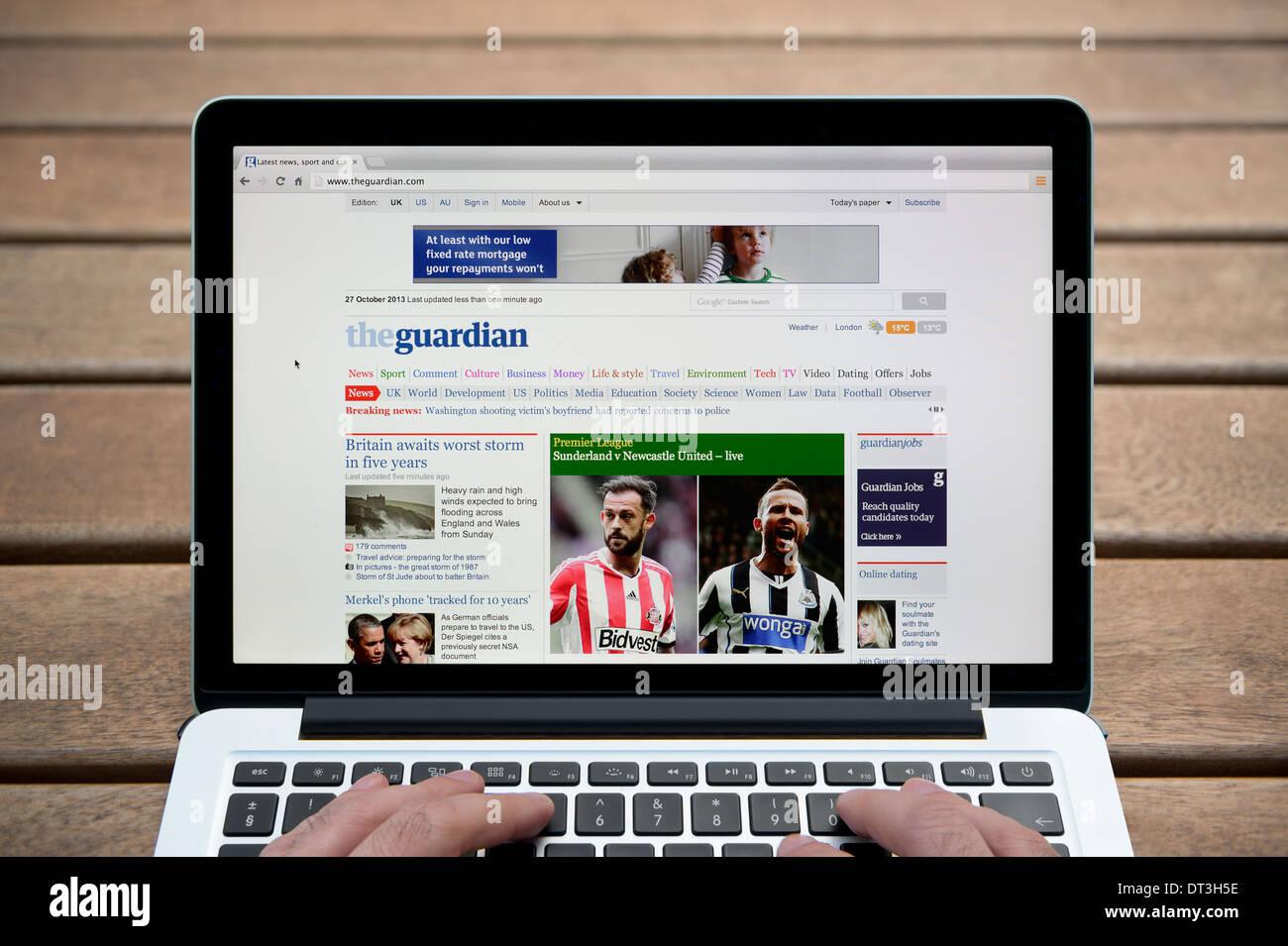 Le gardien site sur un MacBook contre un banc en bois fond de plein air y compris les doigts d'un homme (usage éditorial uniquement). Photo Stock