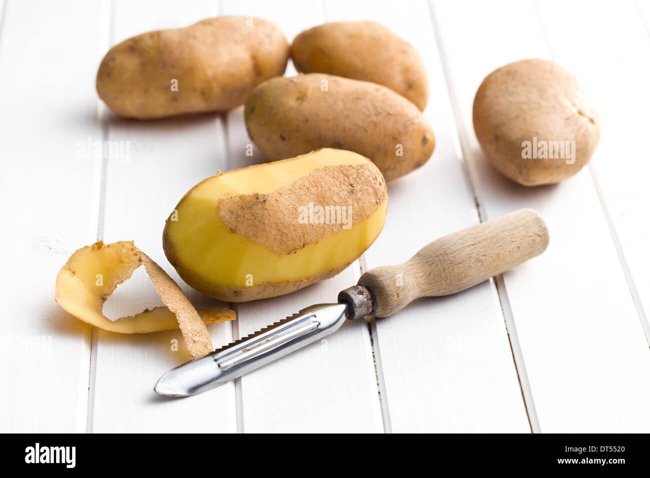 Eplucheur en bois et les pommes de terre sur la table en bois Photo Stock