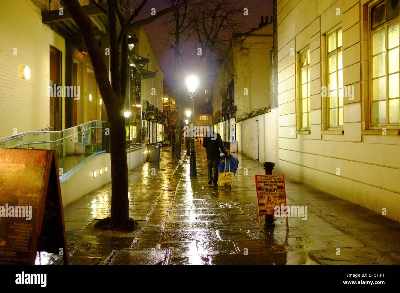 Homme avec une assurance marchant dans une ruelle sur une nuit pluvieuse à Londres Banque D'Images