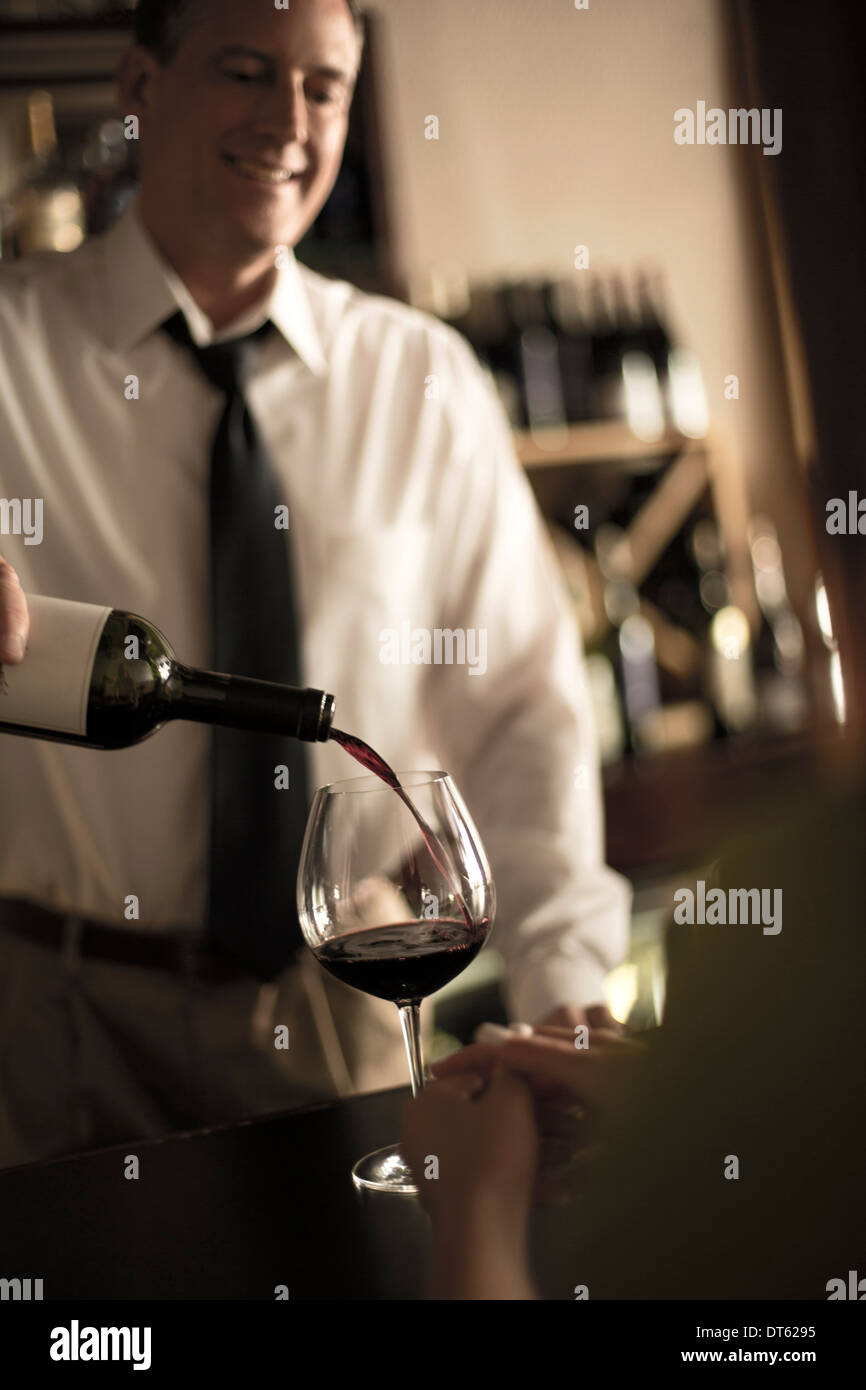 Bartender pouring red wine in bar Photo Stock