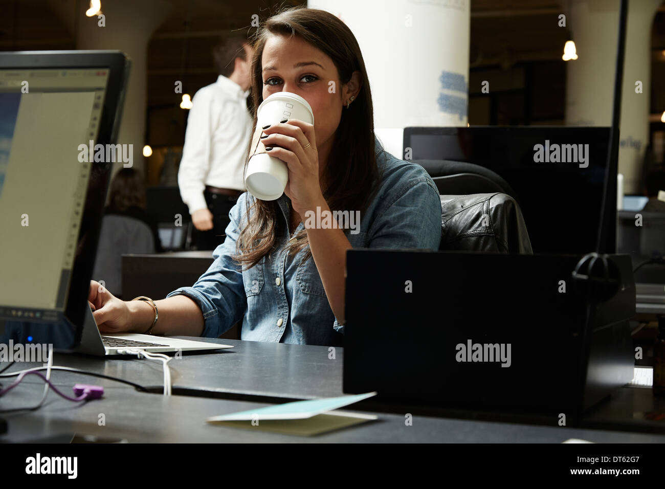 Young woman drinking coffee in office Photo Stock