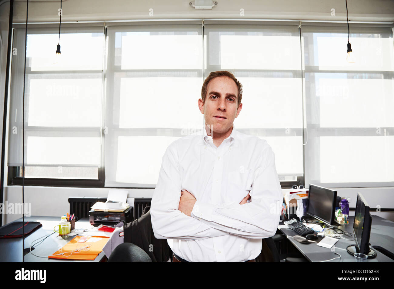 Mid adult man wearing white shirt in office Photo Stock