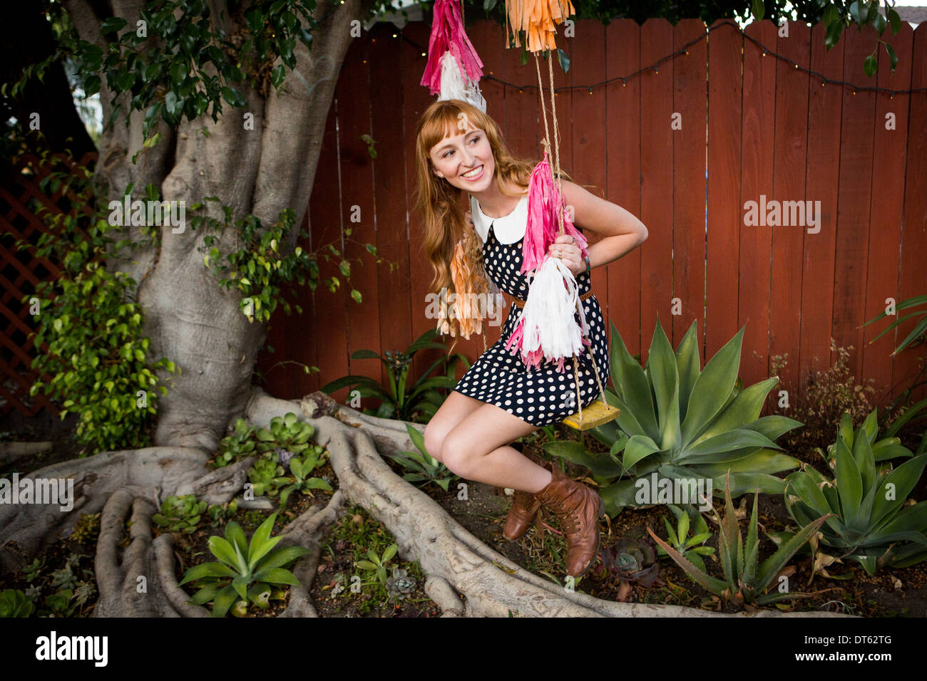 Young woman sitting on swing in garden Photo Stock