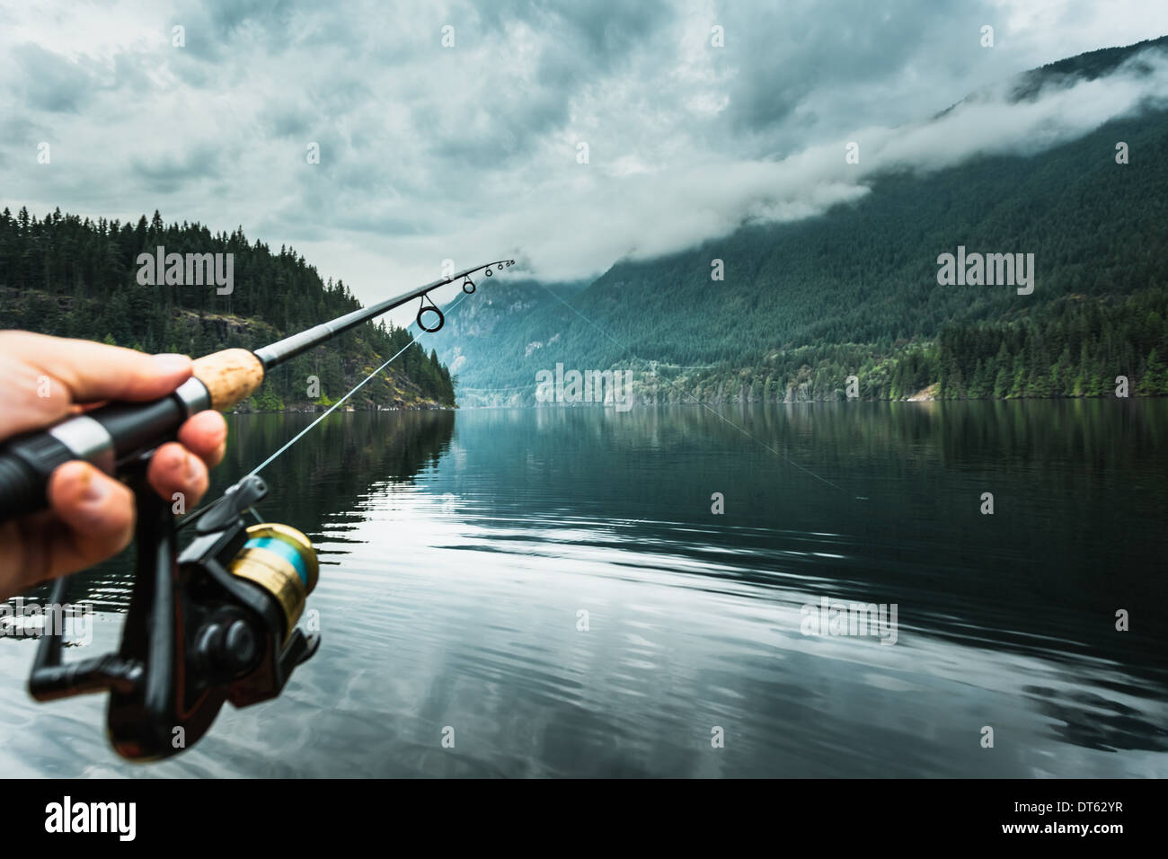 Homme tenant la canne à pêche close-up, Buntzen Lake, British Columbia, Canada Photo Stock