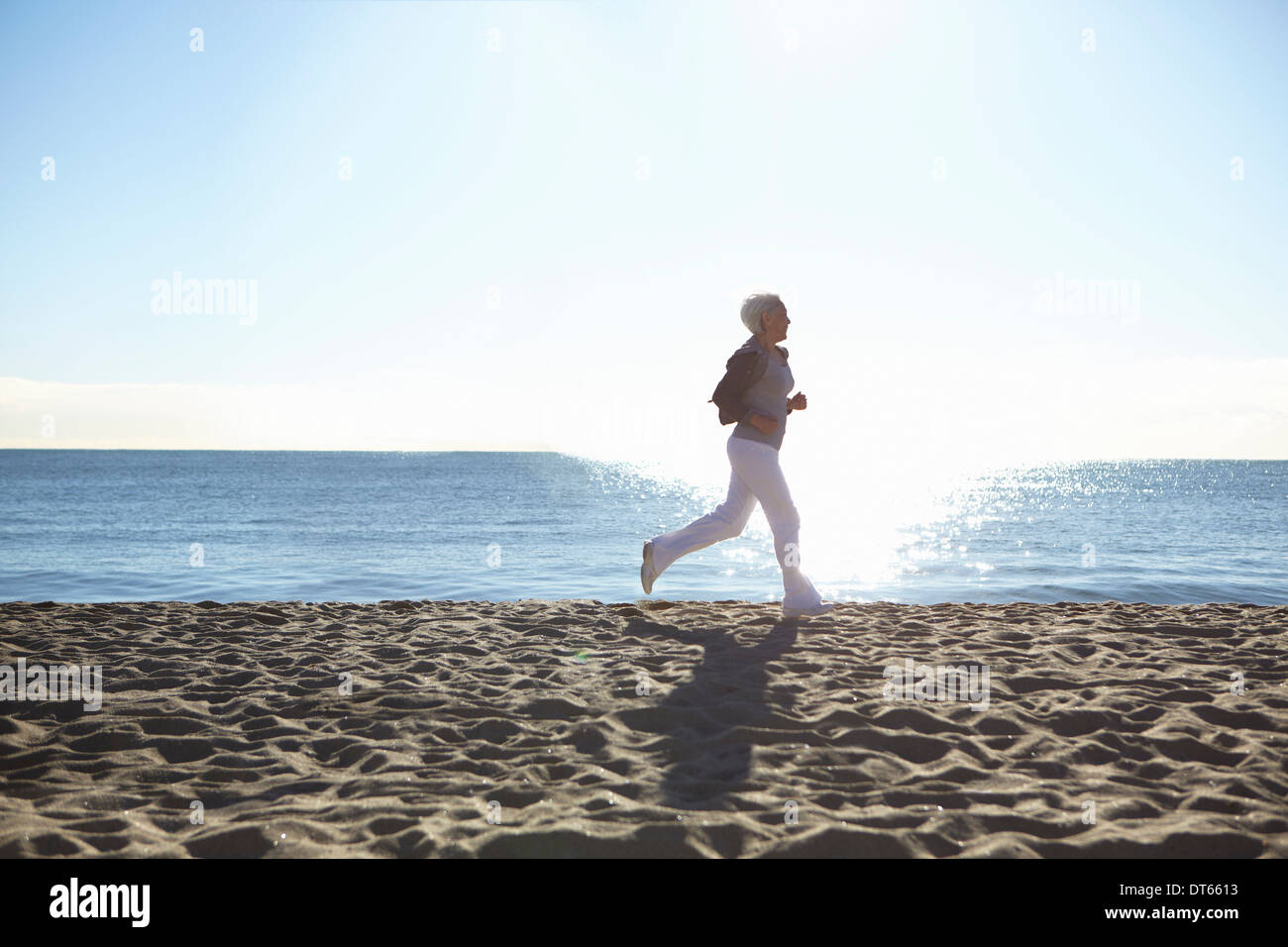 Young woman jogging on beach Photo Stock