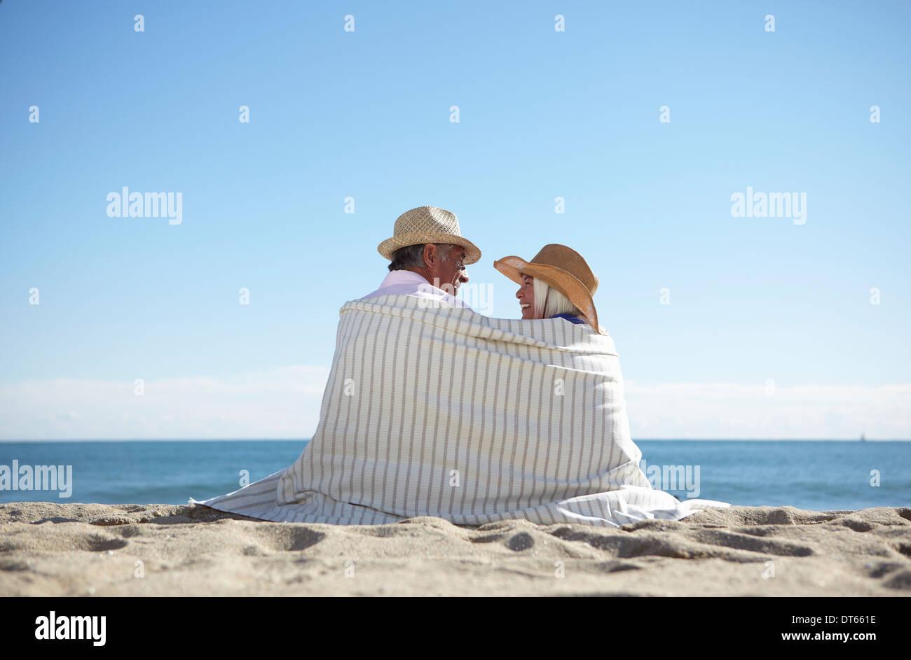 Couple portant des chapeaux de paille sur la plage Banque D'Images