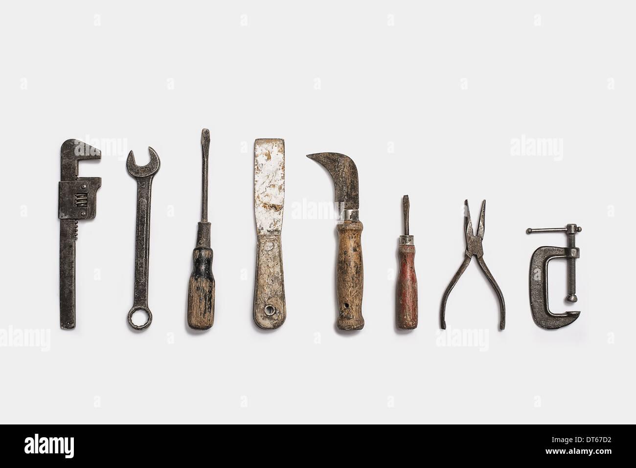 Utilisé des outils disposés dans une rangée. Bien utilisé, usé, poignées en bois en forme de texture lisse. Metal rusty et marqué met en œuvre. Photo Stock