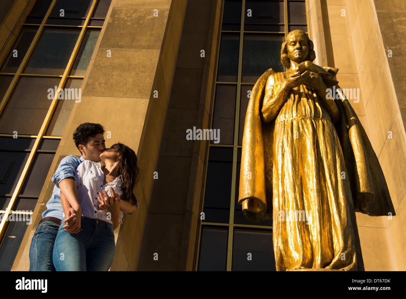 Jeune couple partageant un baiser à côté de la statue, Paris, France Photo Stock