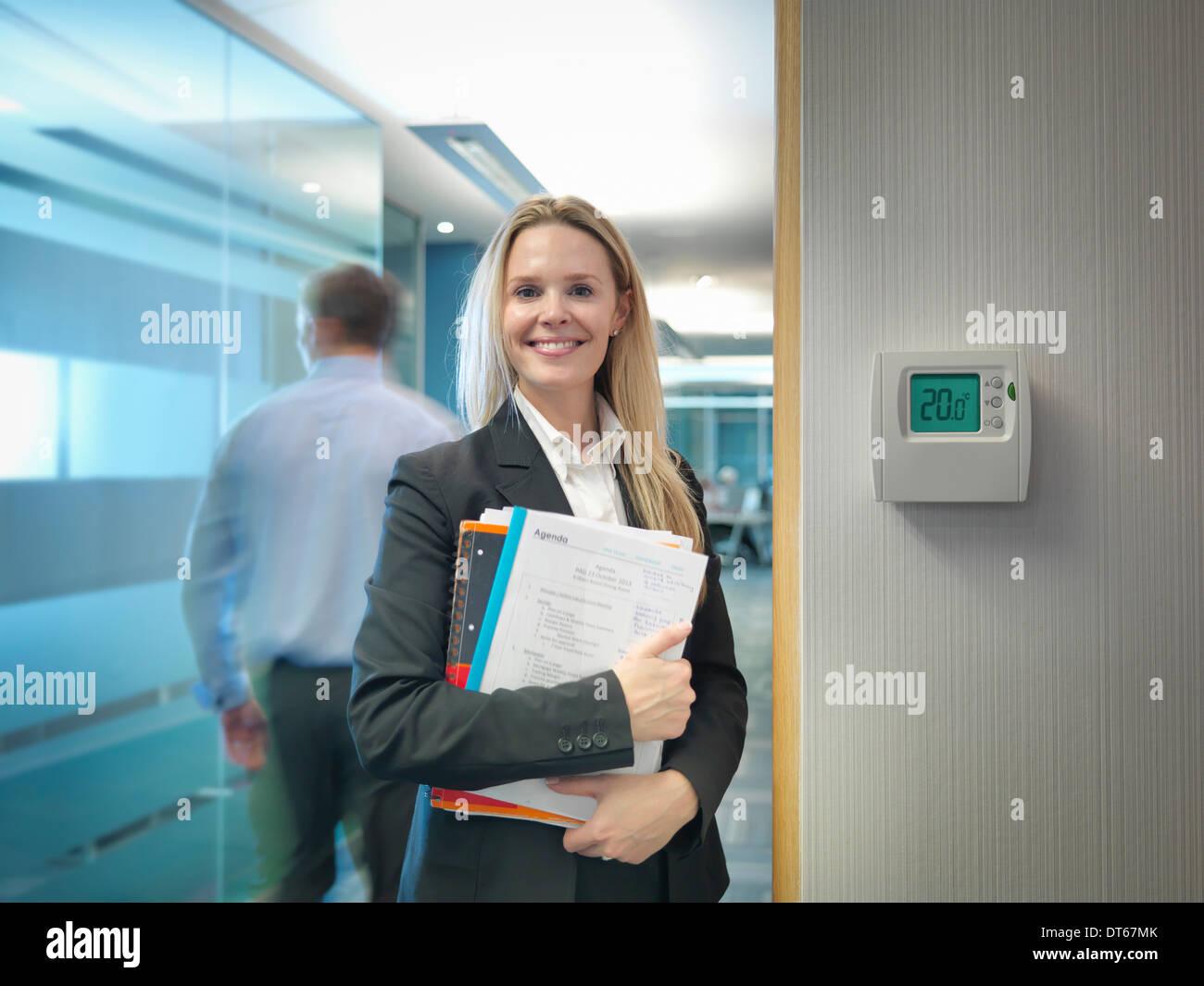 Portrait d'employée de bureau à côté du thermostat bureau ajusté pour réaliser des économies d'énergie Photo Stock