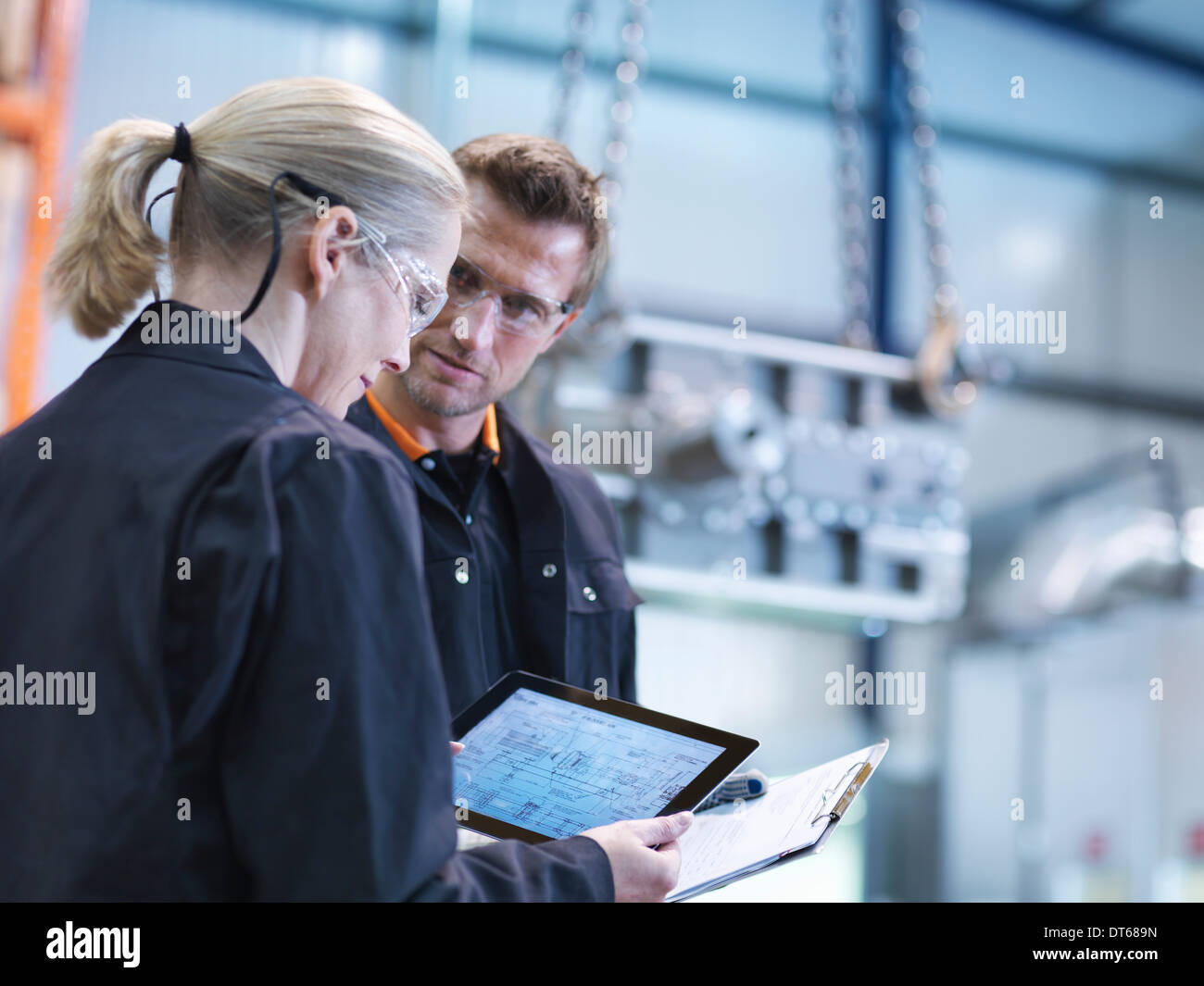 Inspecter les plans des ingénieurs sur digital tablet in engineering factory Photo Stock
