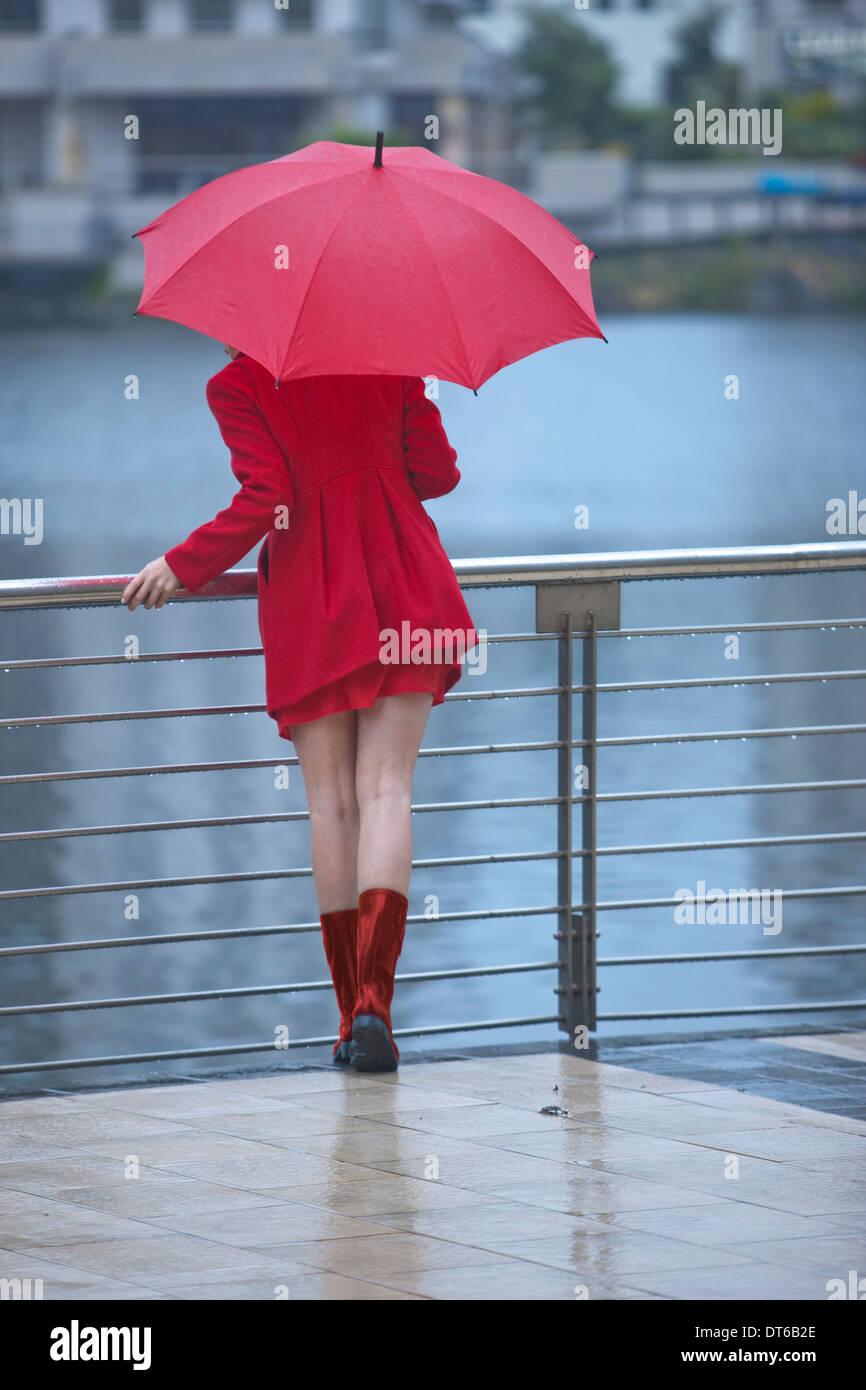 Jeune femme en rouge en attente par waterfront Photo Stock