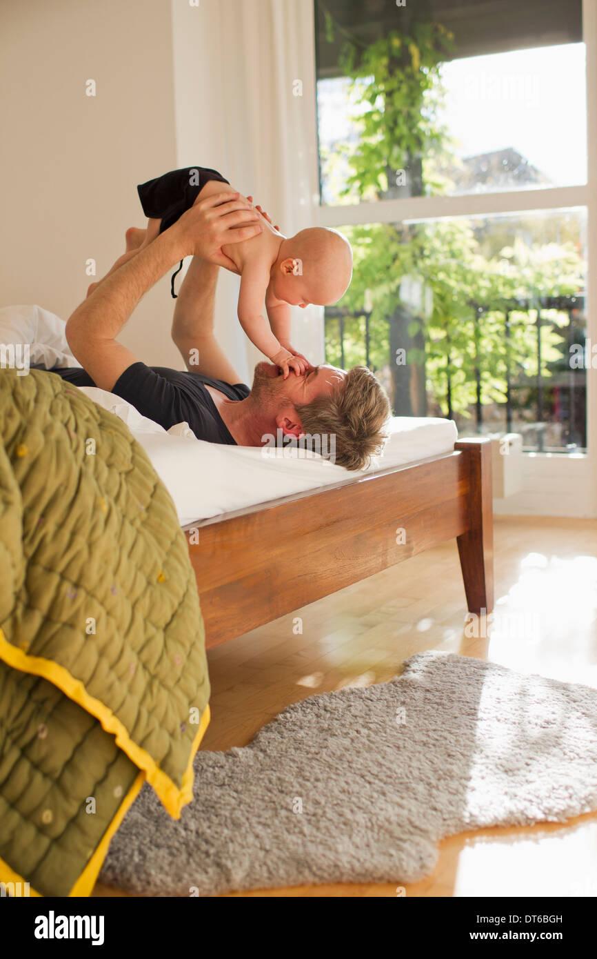 Père fille bébé de levage sur le lit Photo Stock