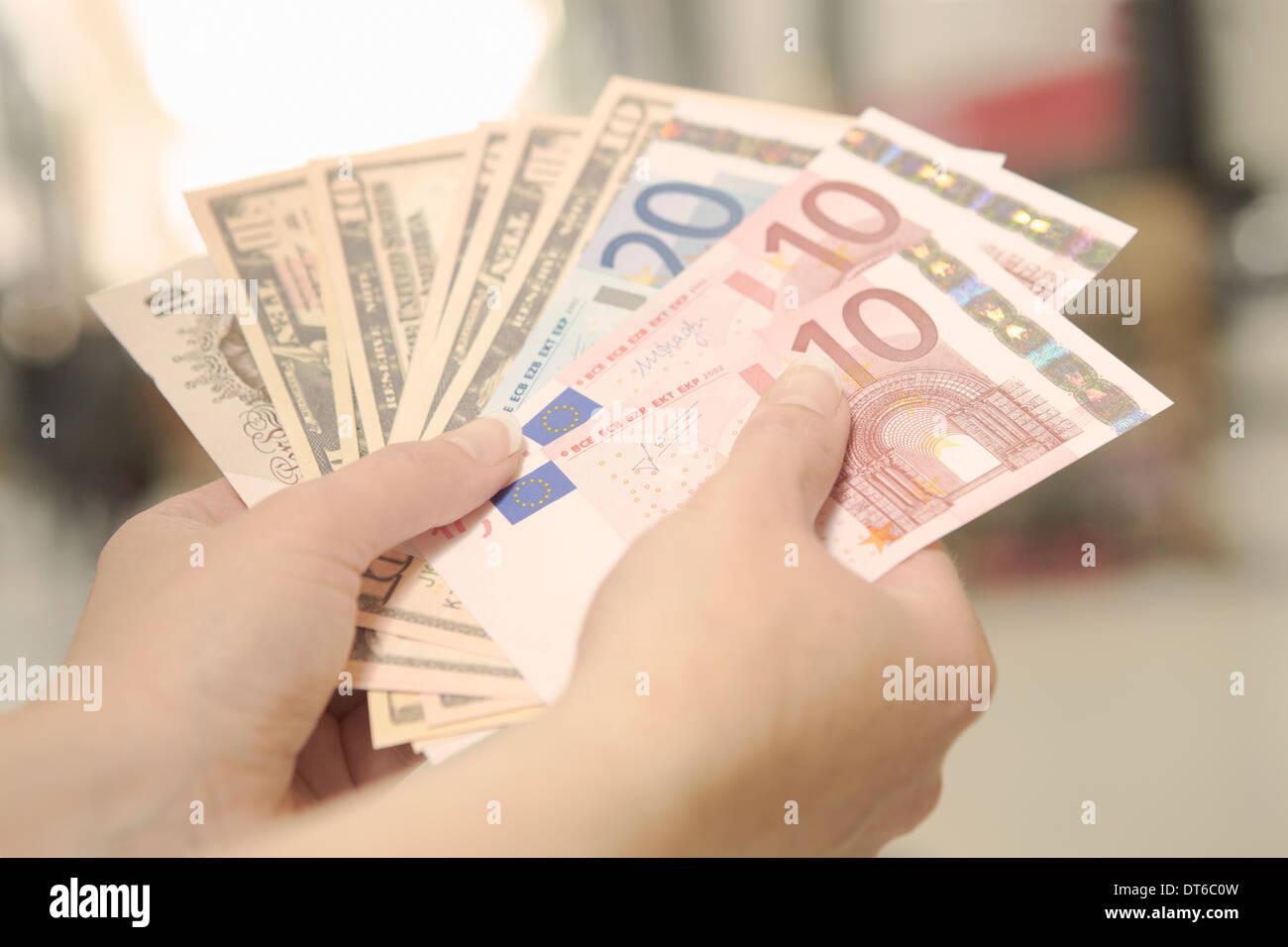 Les mains tenant les Américains, les Britanniques et les billets de banque européens Photo Stock