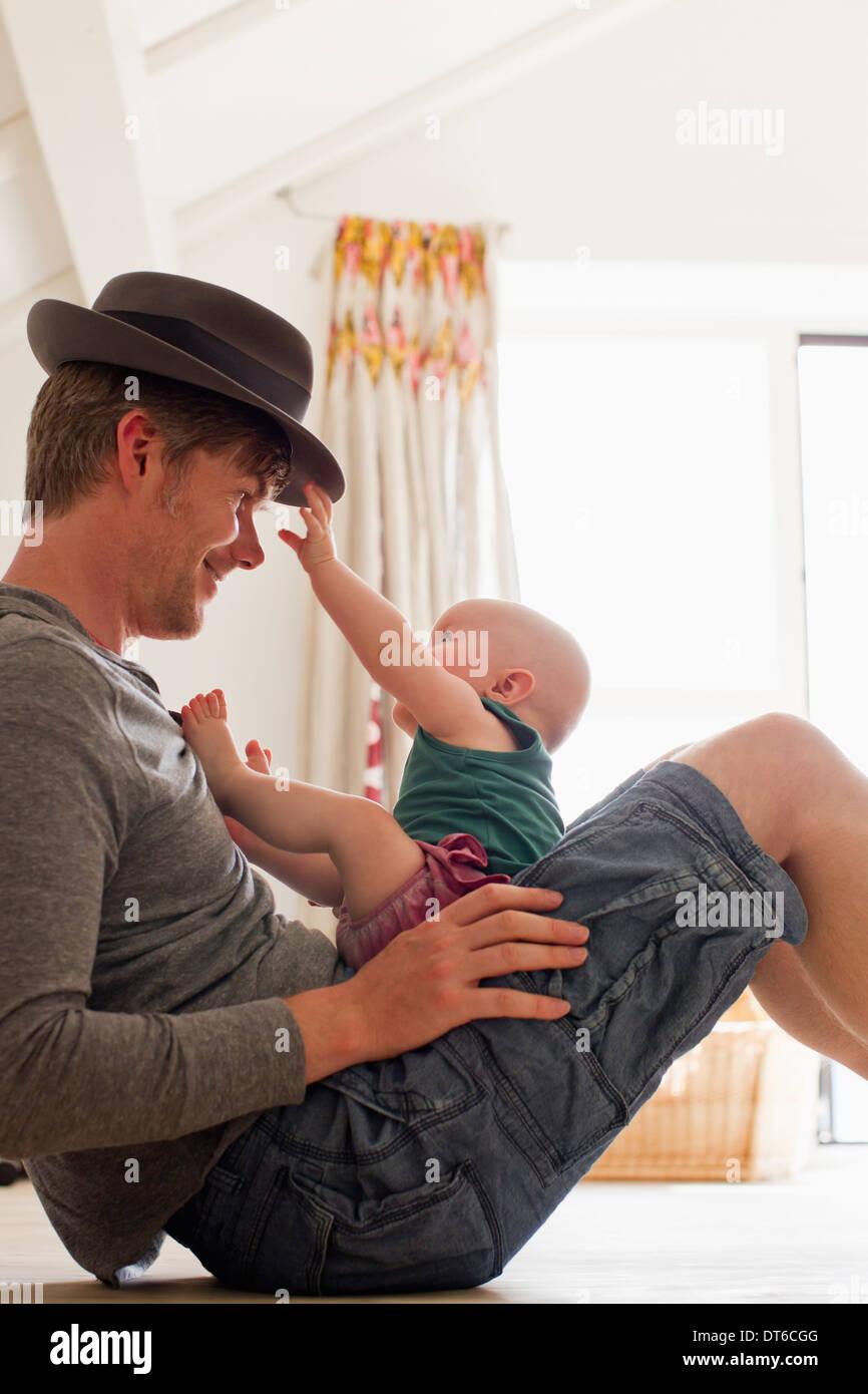 Père wearing hat avec bébé assis sur ses genoux Photo Stock