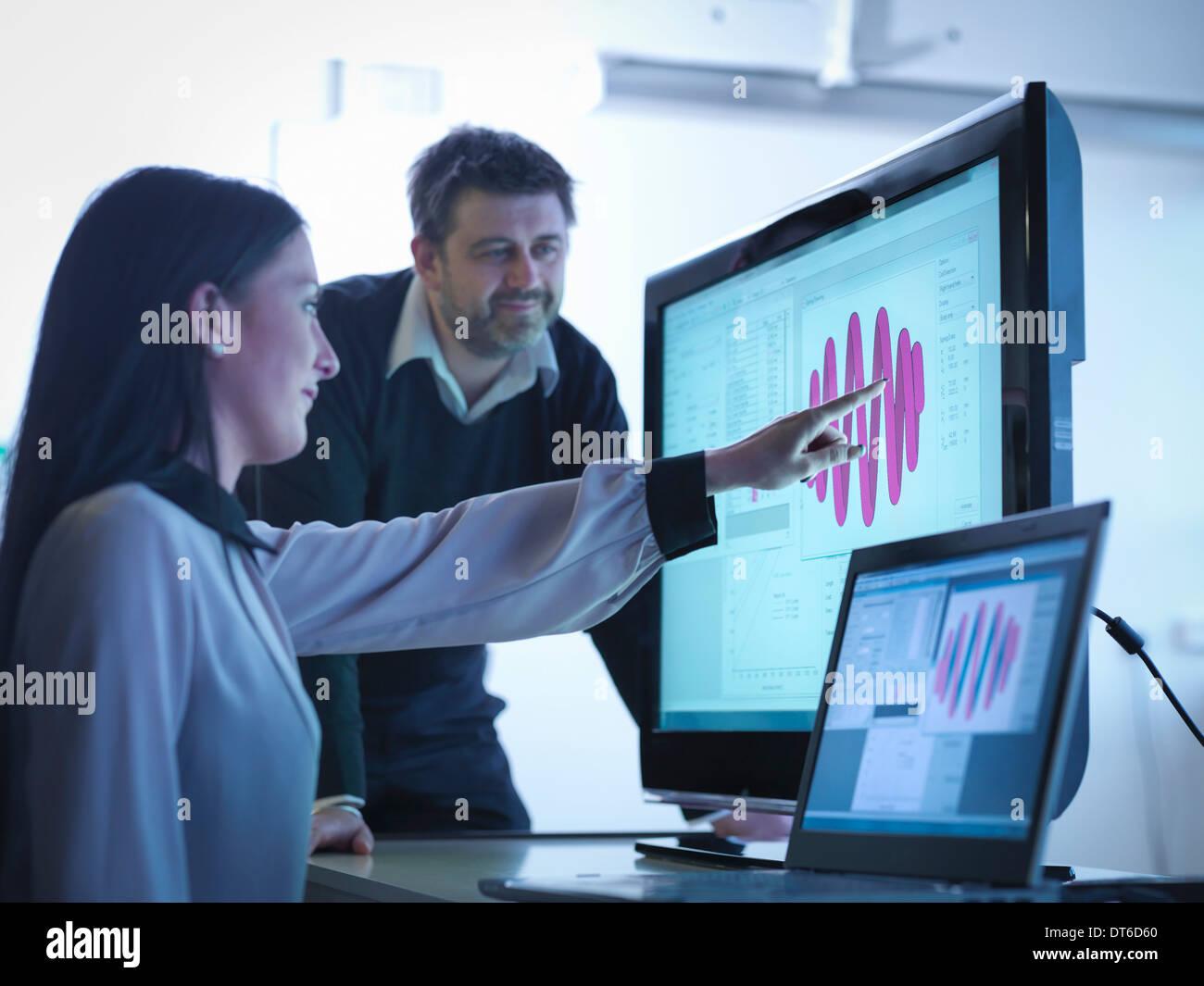 Les travailleurs utilisant un logiciel pour calibrer springs in office Photo Stock