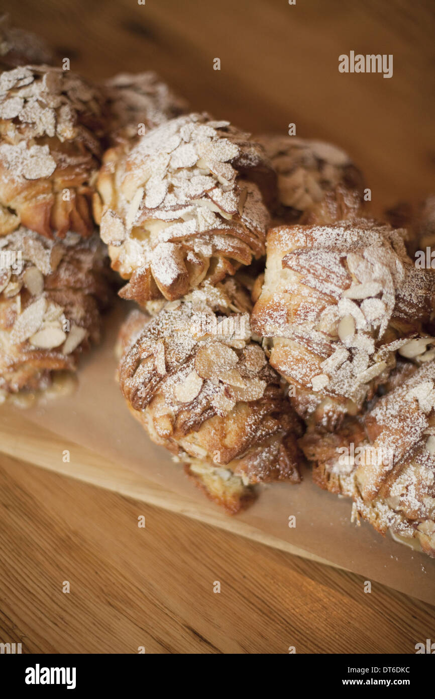 Un groupe de fresh baked croissants aux amandes, sucre à glacer de poussière. Cuisine de fête bio desserts. Photo Stock