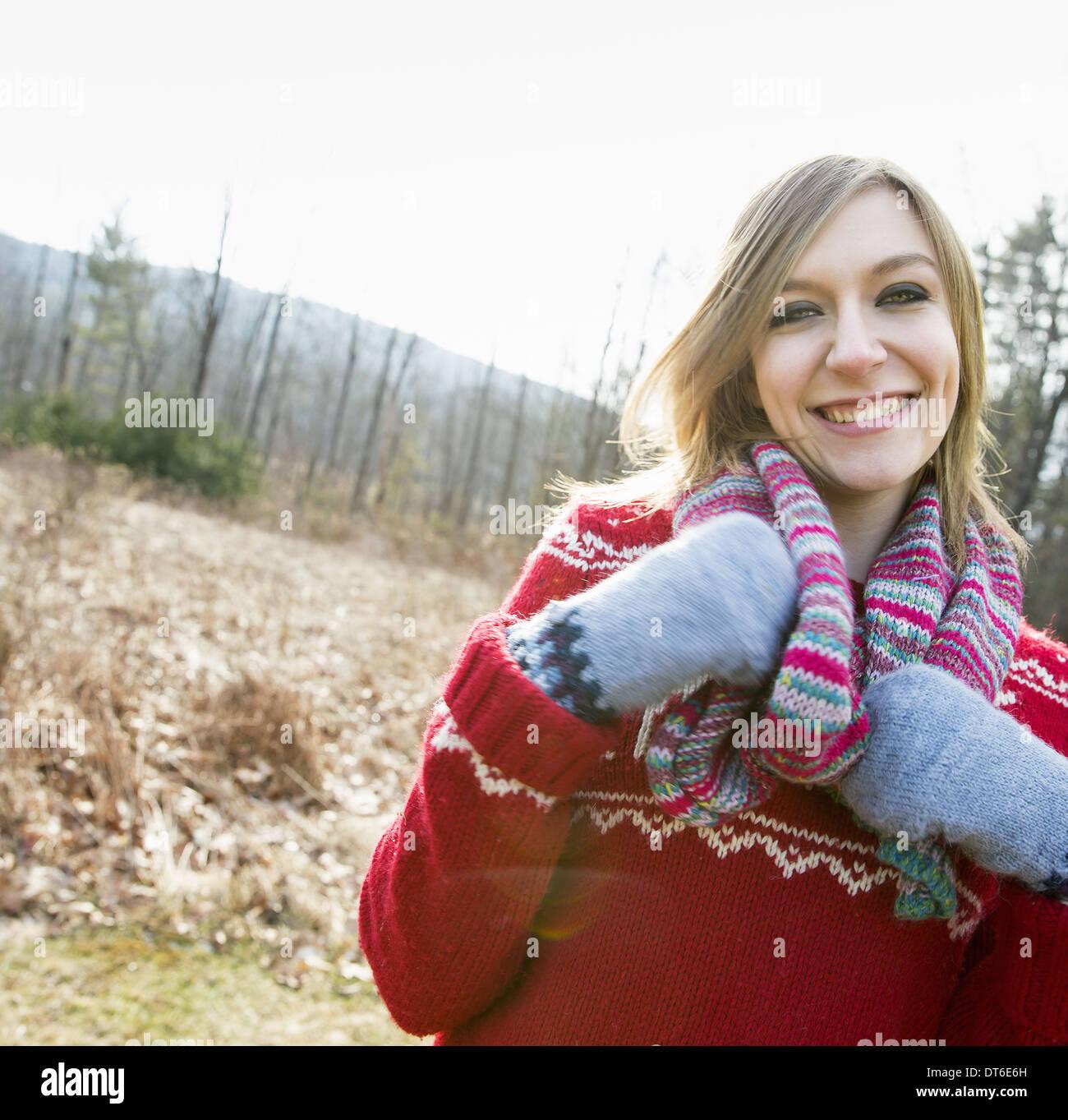 Une femme portant une écharpe en tricot et mitaines de laine à l'extérieur sur une journée d'hiver. Photo Stock