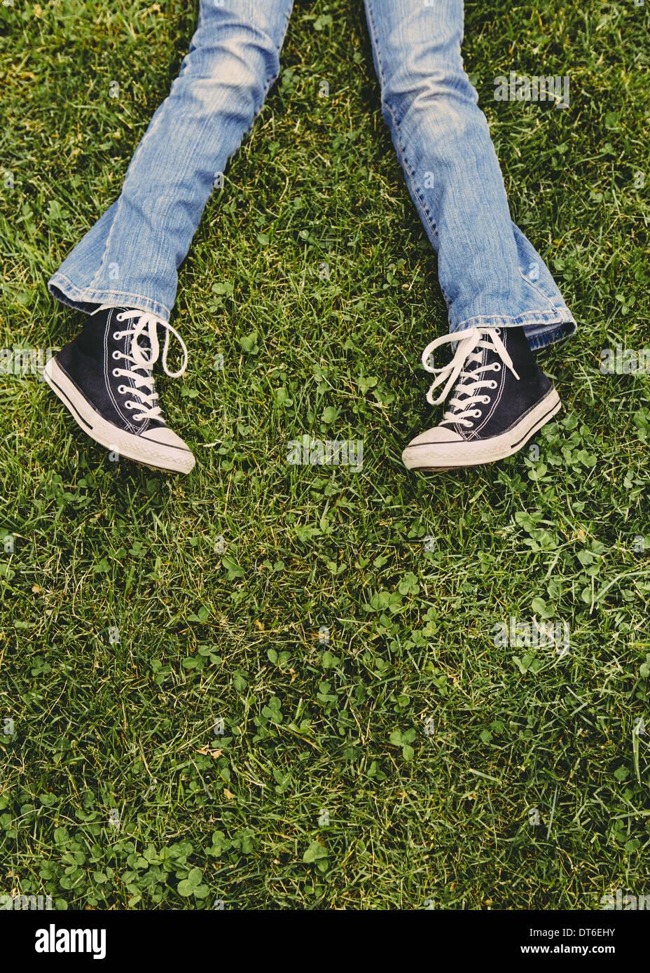 Une fillette de dix ans couché dans l'herbe. Portrait de sa partie inférieure des jambes. Porter des chaussures et des jeans bleu délavé. Photo Stock