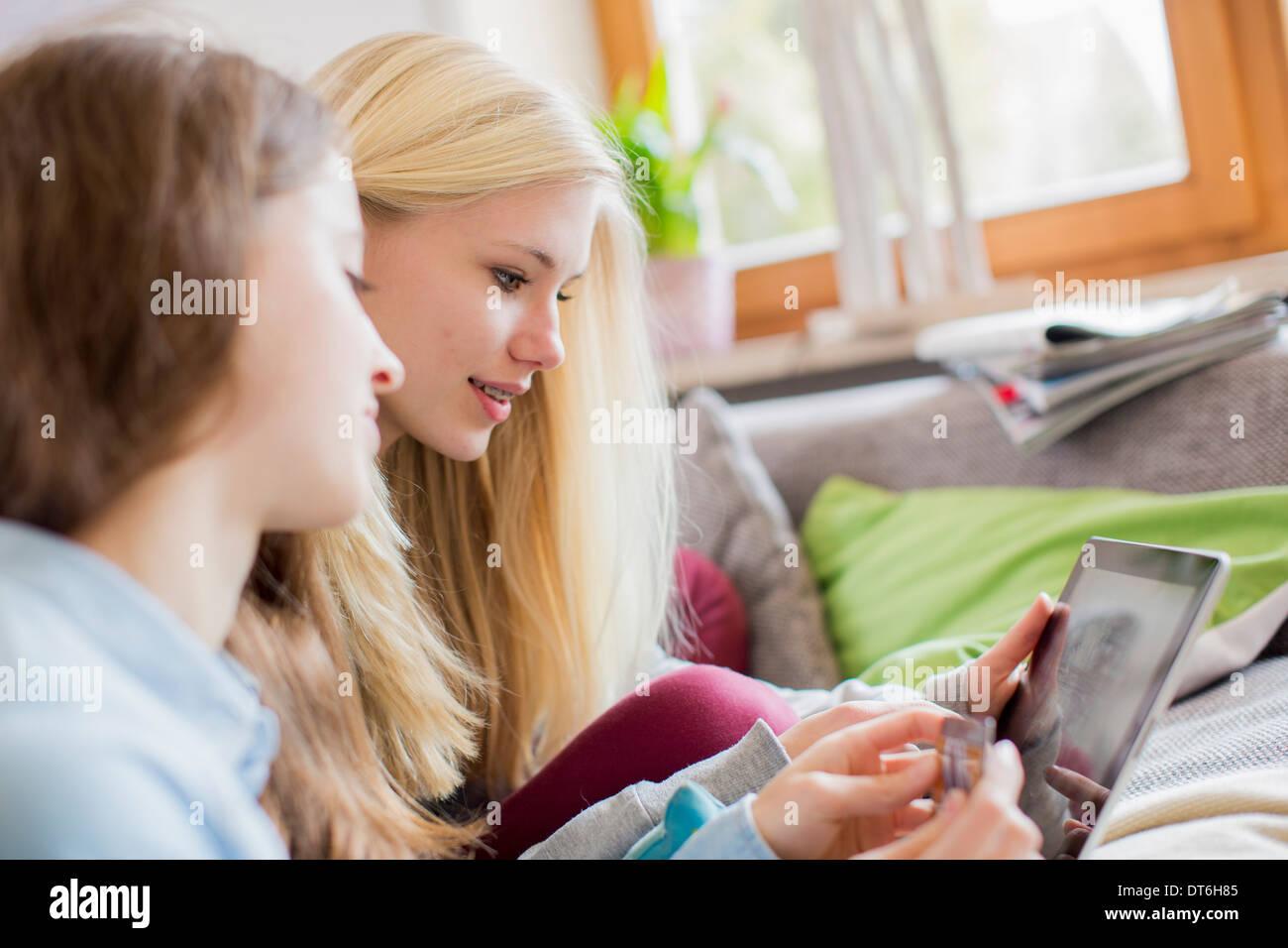 Teenage Girls using tablet pour les achats en ligne Photo Stock