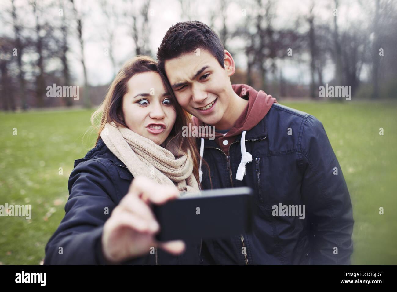 Drôle de couple photographing themselves with smart phone dans le parc. Jolie jeune fille avec son petit ami à prendre des photos. Photo Stock
