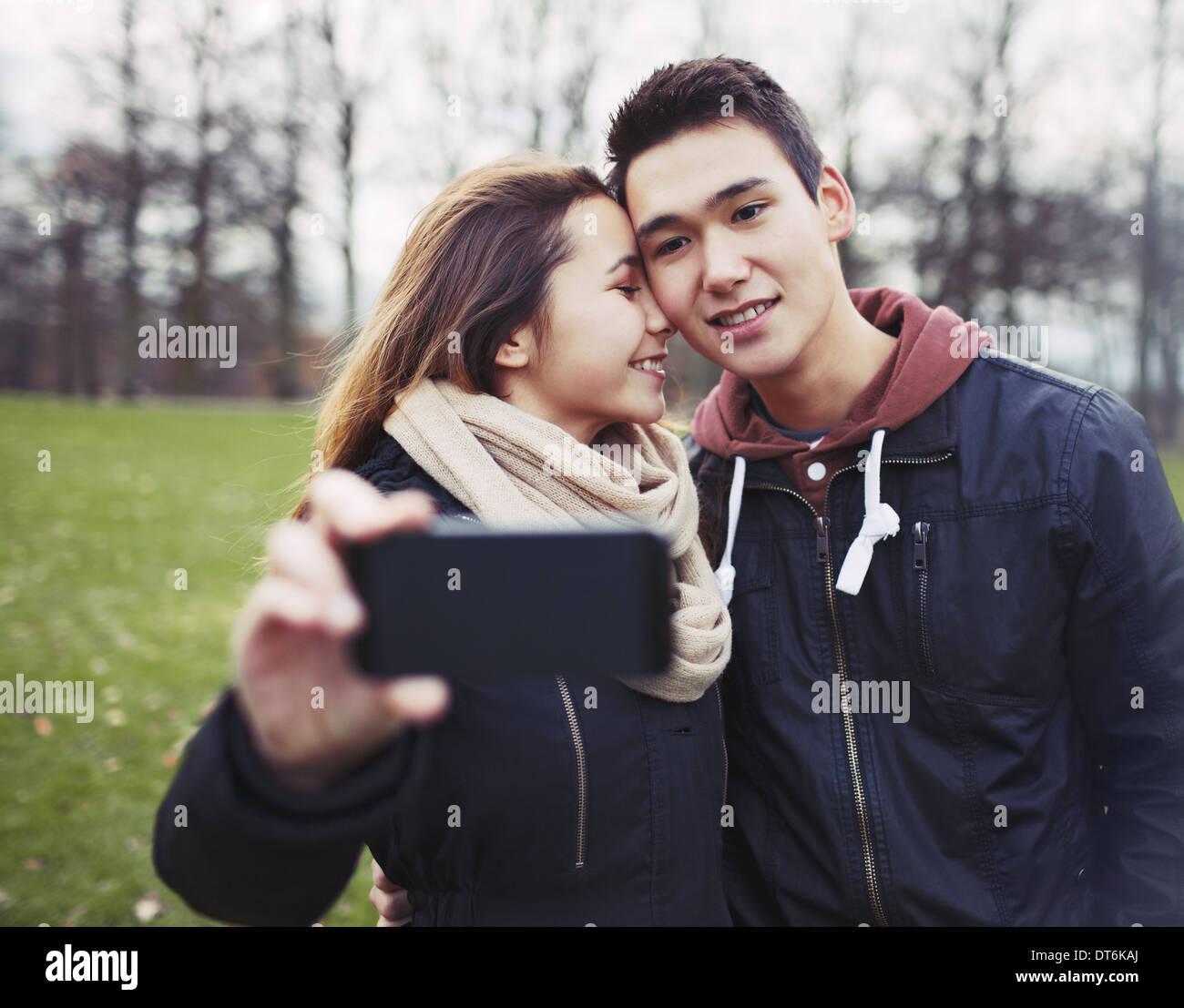 Young couple taking pictures en utilisant un téléphone intelligent au parc. Teenage boy and girl in love photographier eux-mêmes Photo Stock