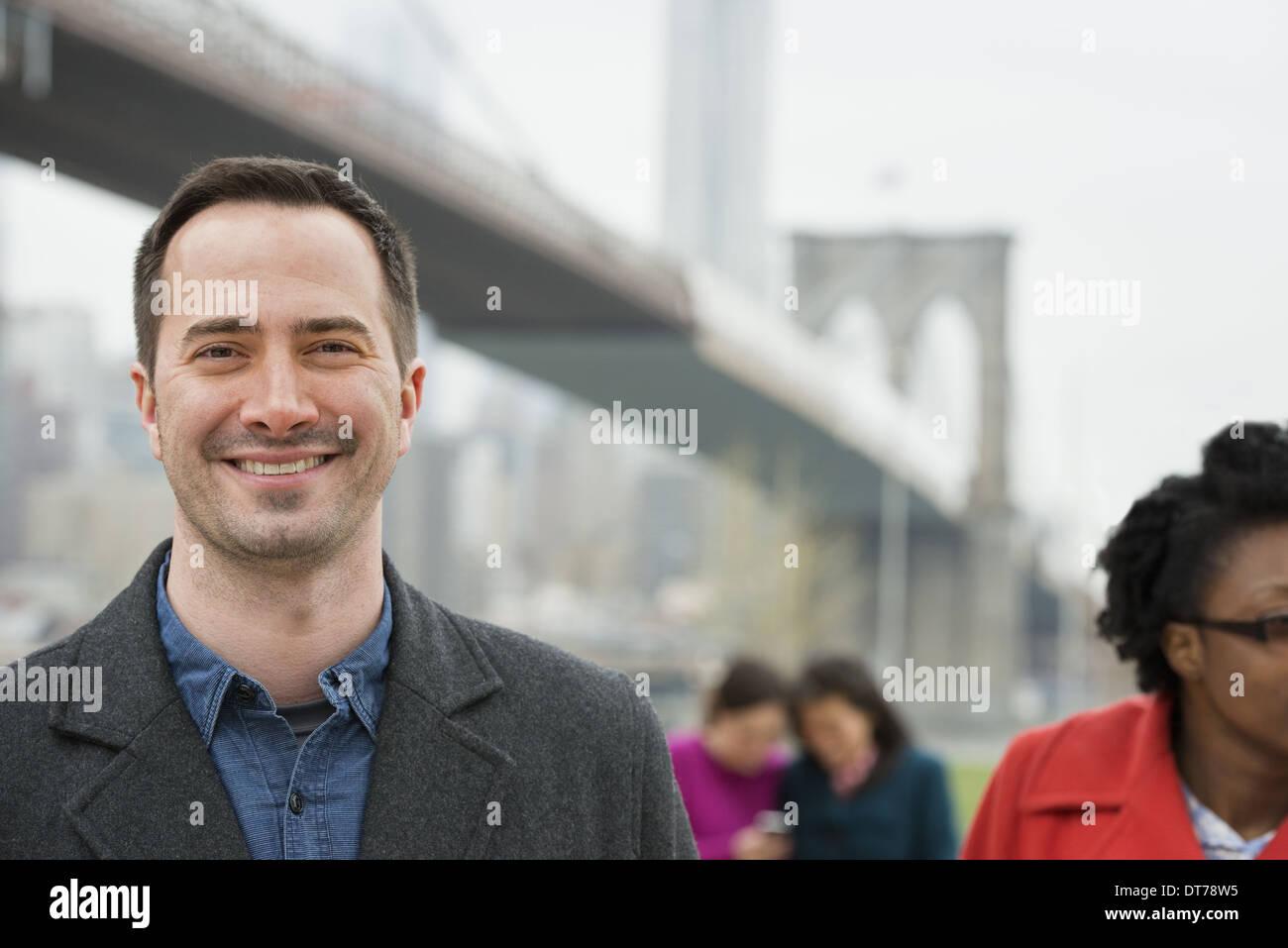 Passage sur la East River. Quatre personnes, deux femmes à la recherche à un téléphone intelligent, et un homme et une femme au premier plan. Photo Stock